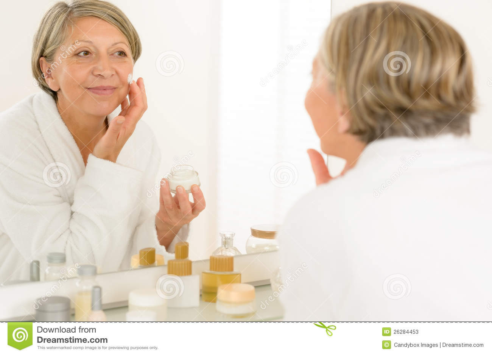 Reflexión mayor de la mujer en espejo del cuarto de baño