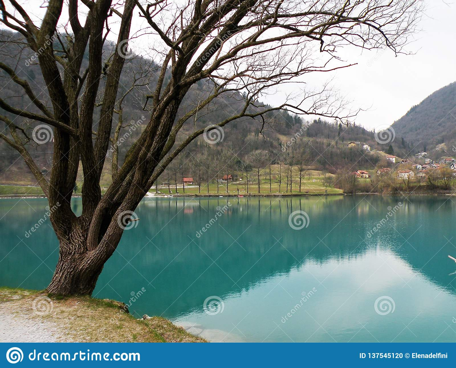 Reflexion av kullar och by och himmel