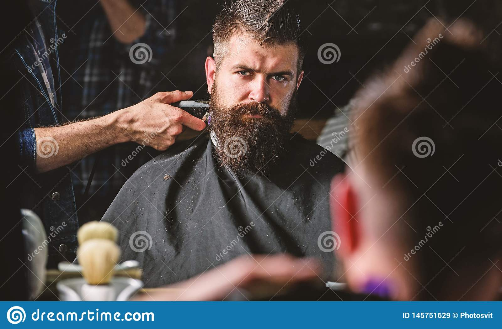 Reflexion of barbers hand with hair clipper trimming nape of client. Hipster bearded client getting hairstyle in front
