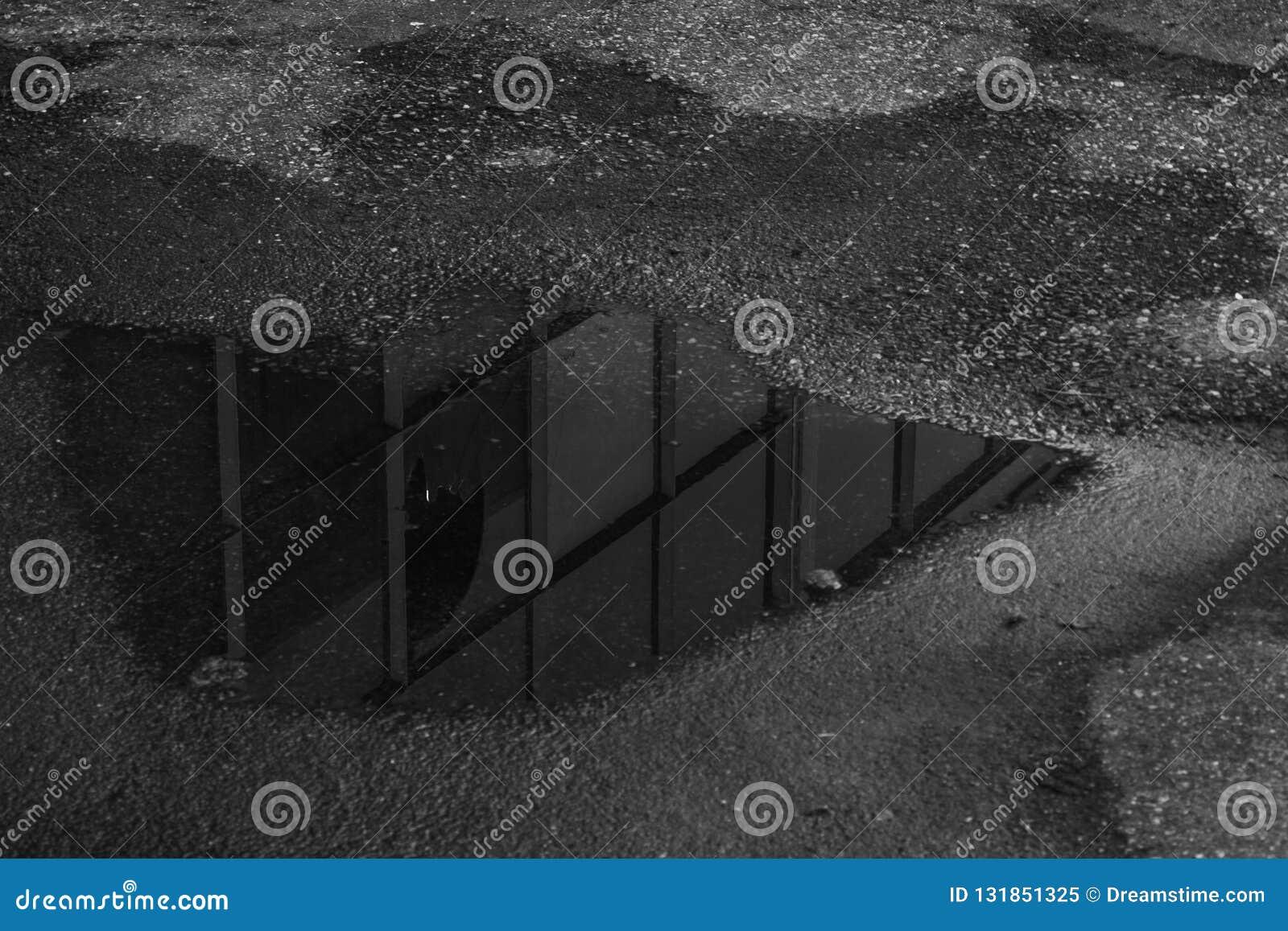 Reflexion eines Gebäudes in einer Pfütze