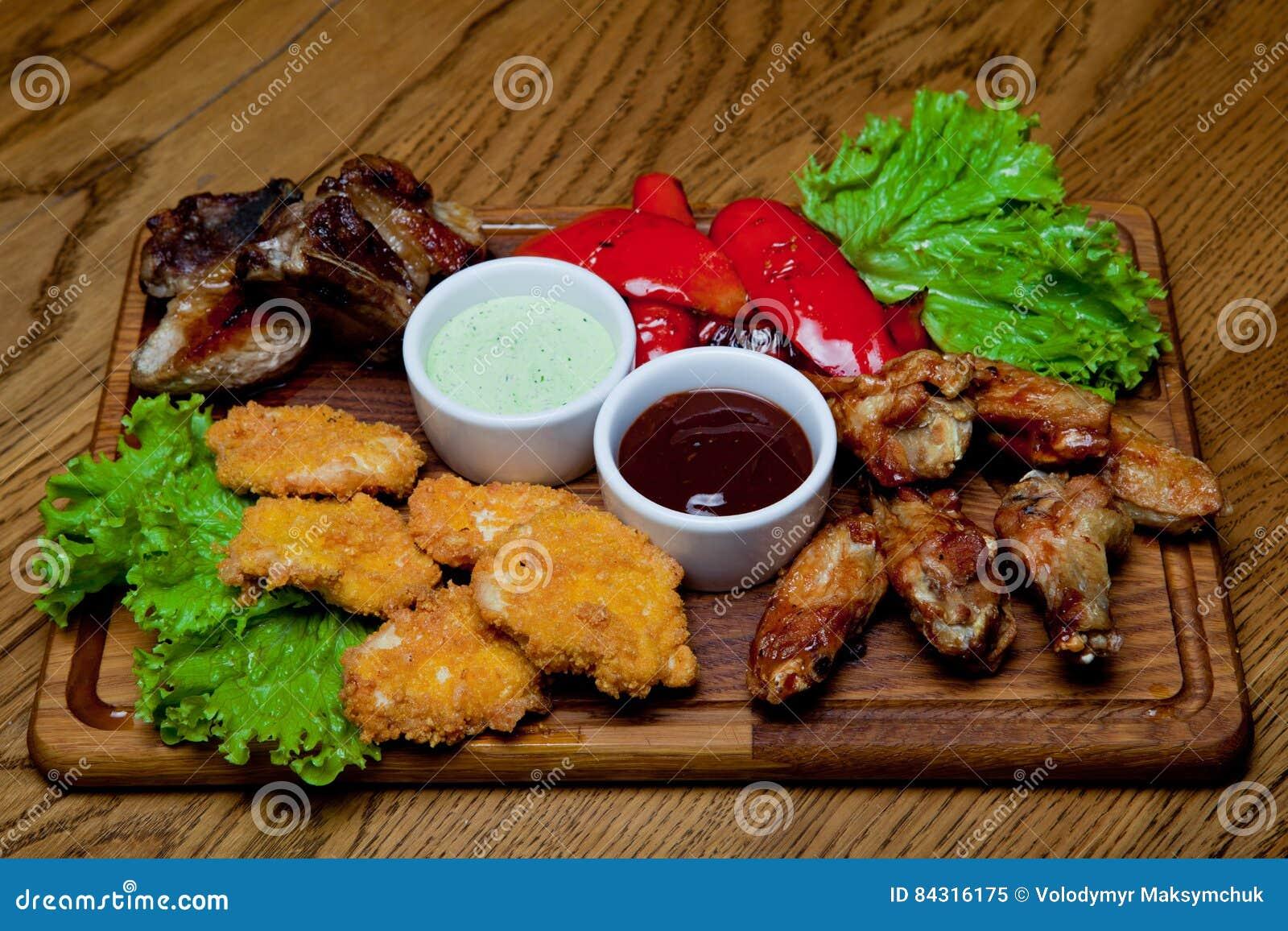 Reforços de carne de porco com molho do mel, asas de galinha picantes, pimentas grelhadas