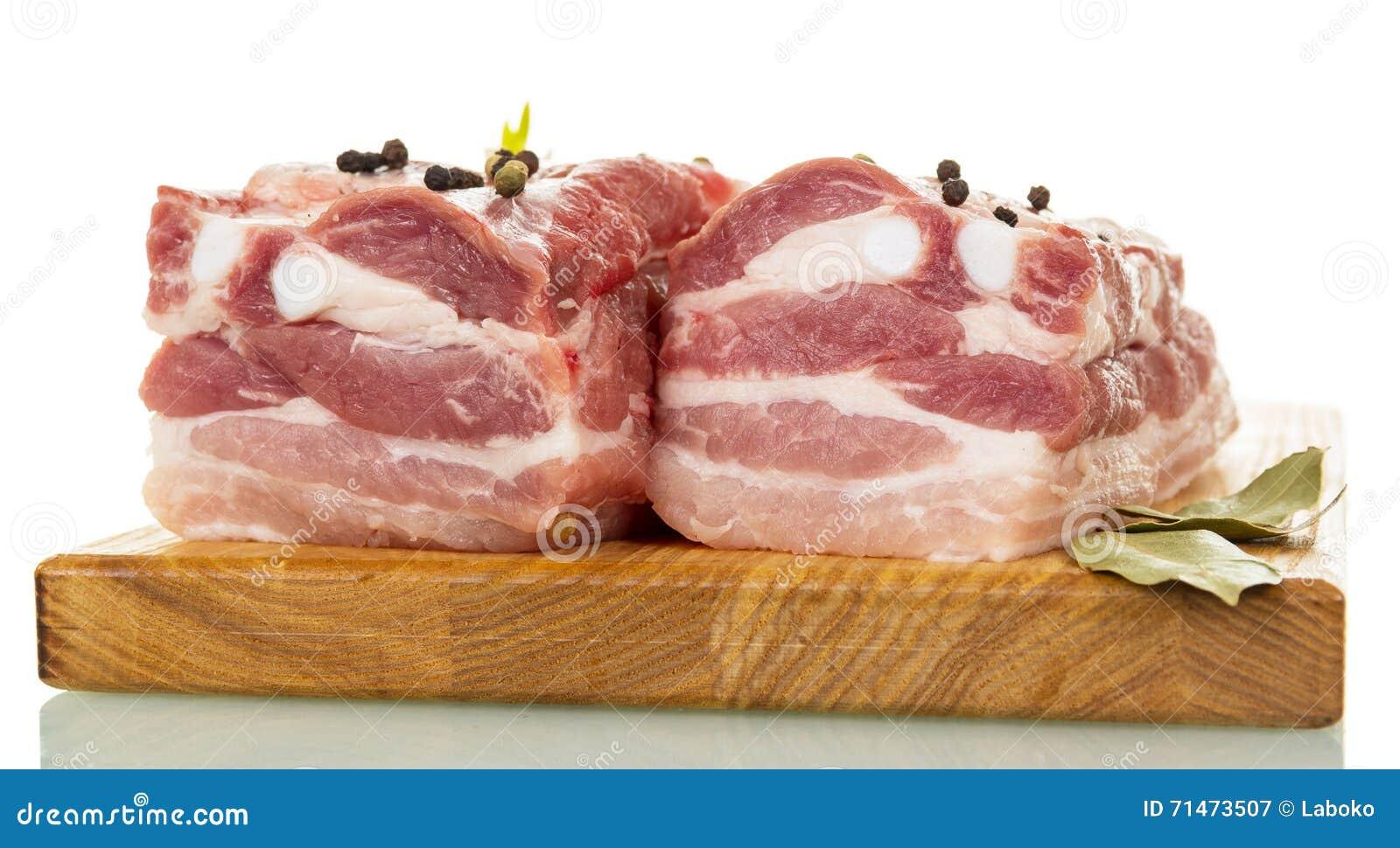 Reforços de carne de porco crus com as especiarias isoladas no branco