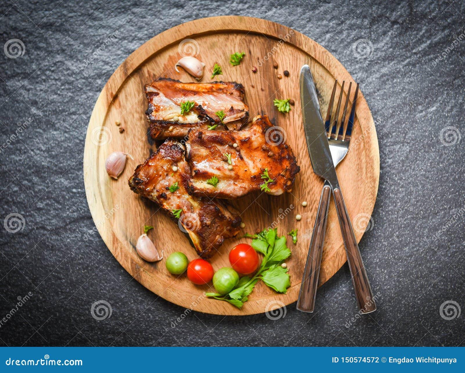 Reforços de carne de porco do BBQ grelhados com ervas e especiarias dos tomates na bandeja de madeira - a entrecosto de porco de