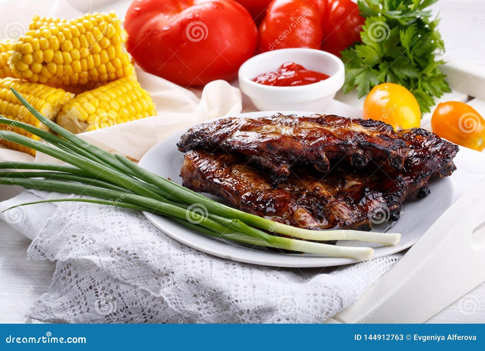 Refor?os de carne de porco grelhados Os refor?os do BBQ da carne serviram com molho e os legumes frescos