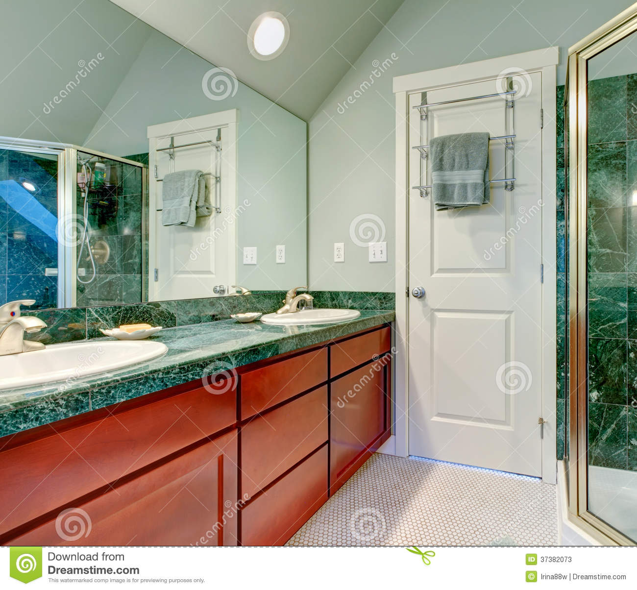 green bathroom with vaulted ceiling tile floor and brown cabinets