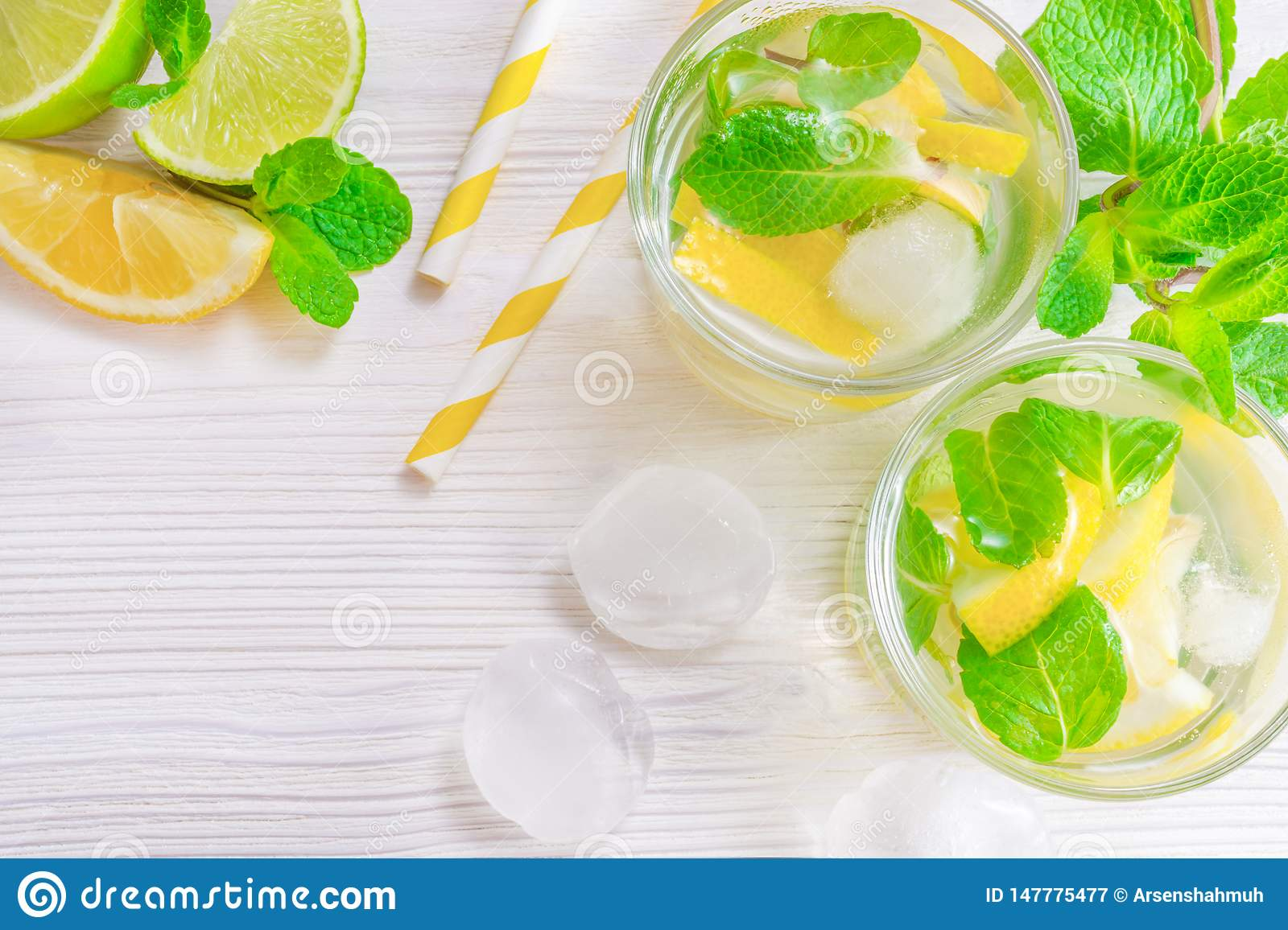 Refreshing summer drink mojito with lime, lemon and mint, with ice cubes on white wooden background. Flat-lay, top view