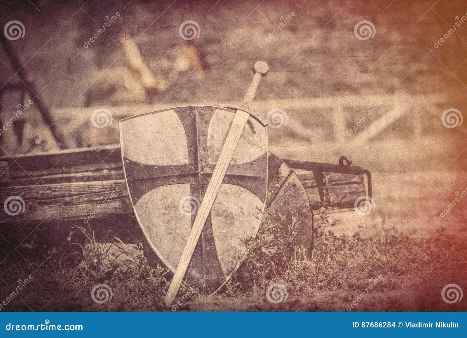 Refresque la espada metálica y el escudo pesado en los vagos del carro de las Edades Medias