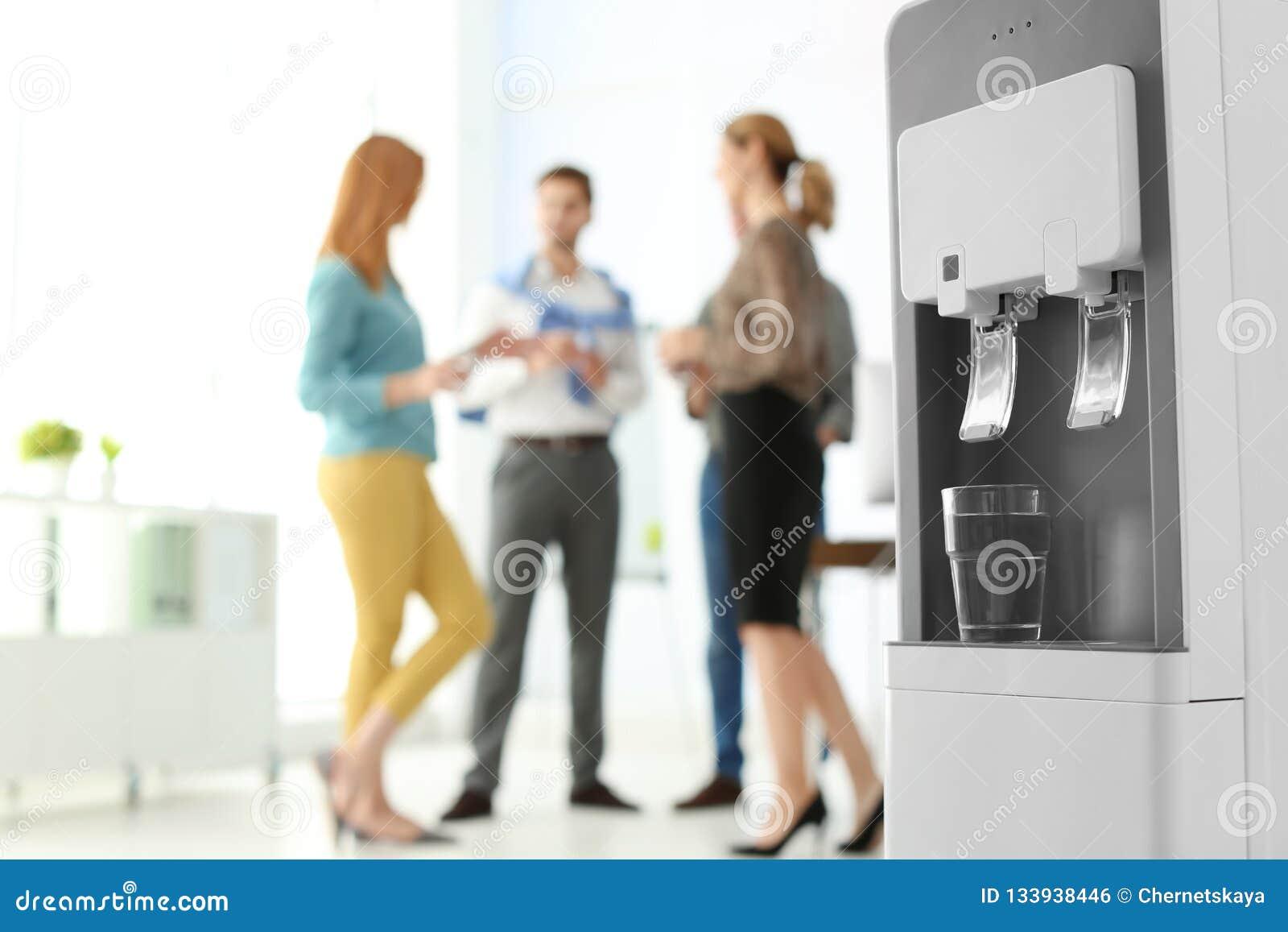 Refrigerador de agua moderno con los empleados de oficina de cristal y borrosos en fondo