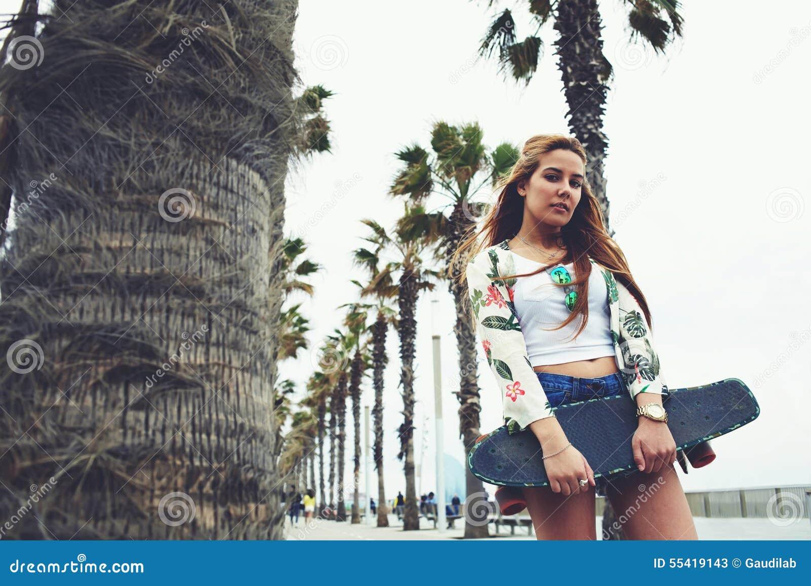 Refroidissez la femme à la mode posant avec son long conseil pendant la promenade de récréation en été
