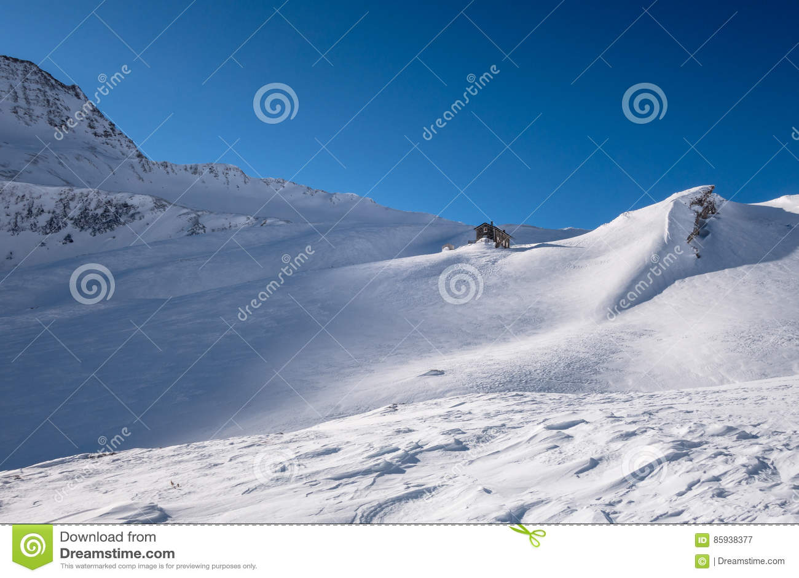 Refugio alpino debajo del canto de la montaña en invierno en nieve azotada por el viento