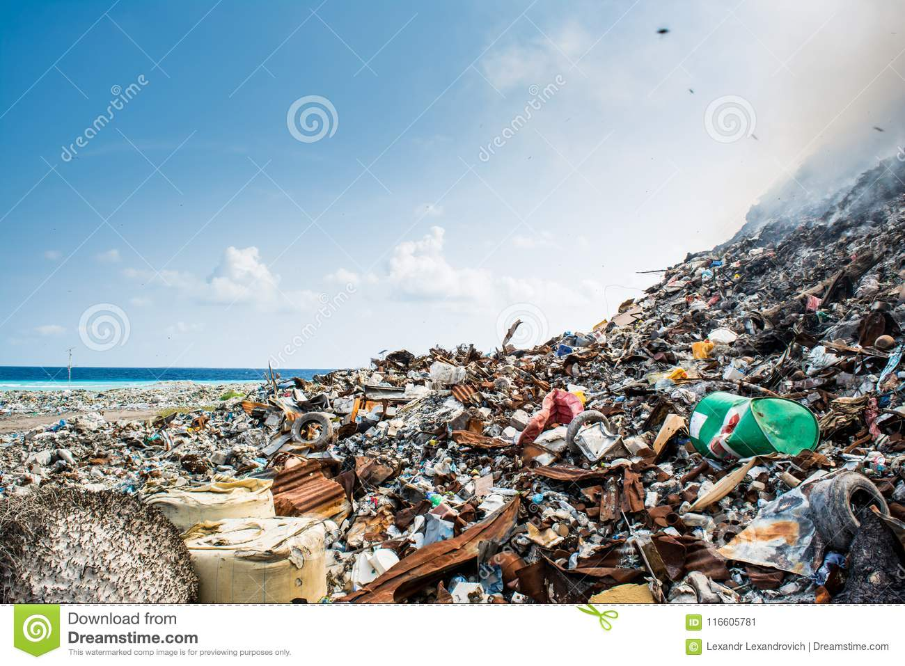Refuse at the garbage dump full of smoke, litter, plastic bottles,rubbish and trash at tropical island