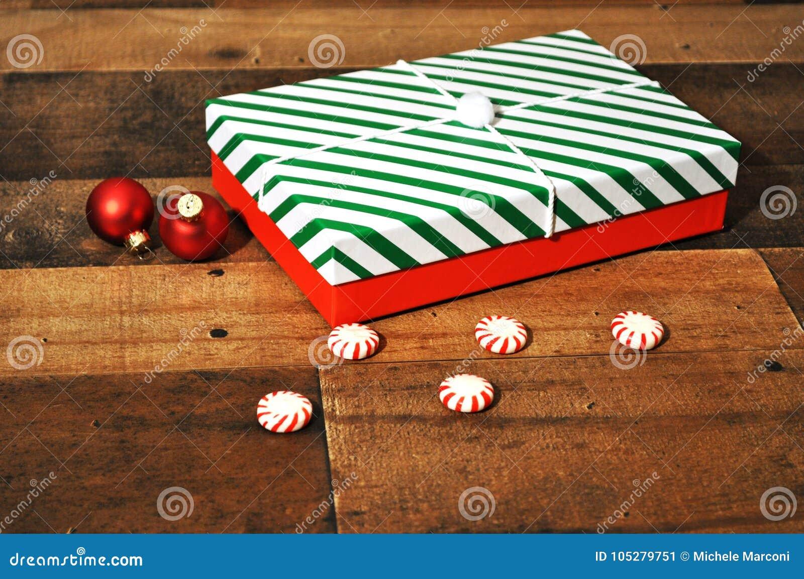 Regali di Natale avvolti in carta a strisce bianca e verde rossa di festa