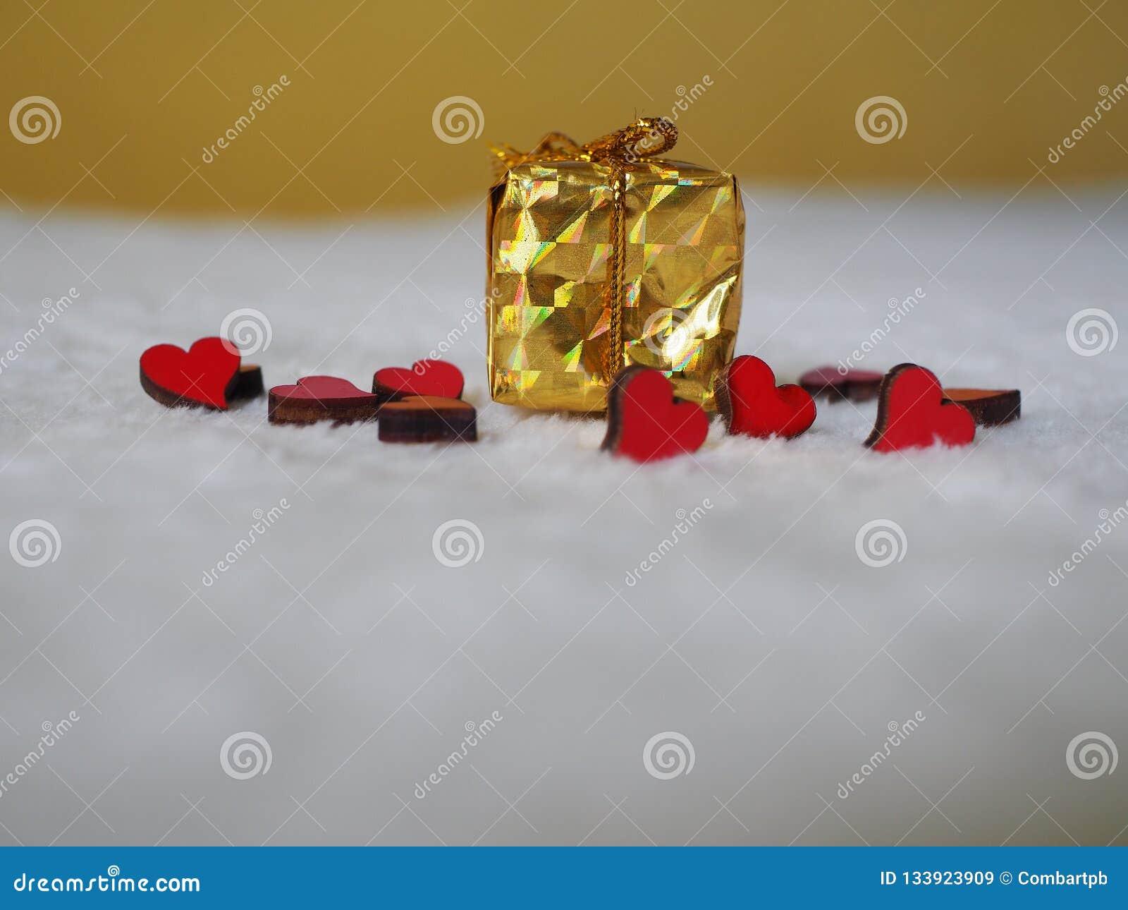 Regalo de la Navidad con los corazones rojos en el fondo blanco, lugar para el texto