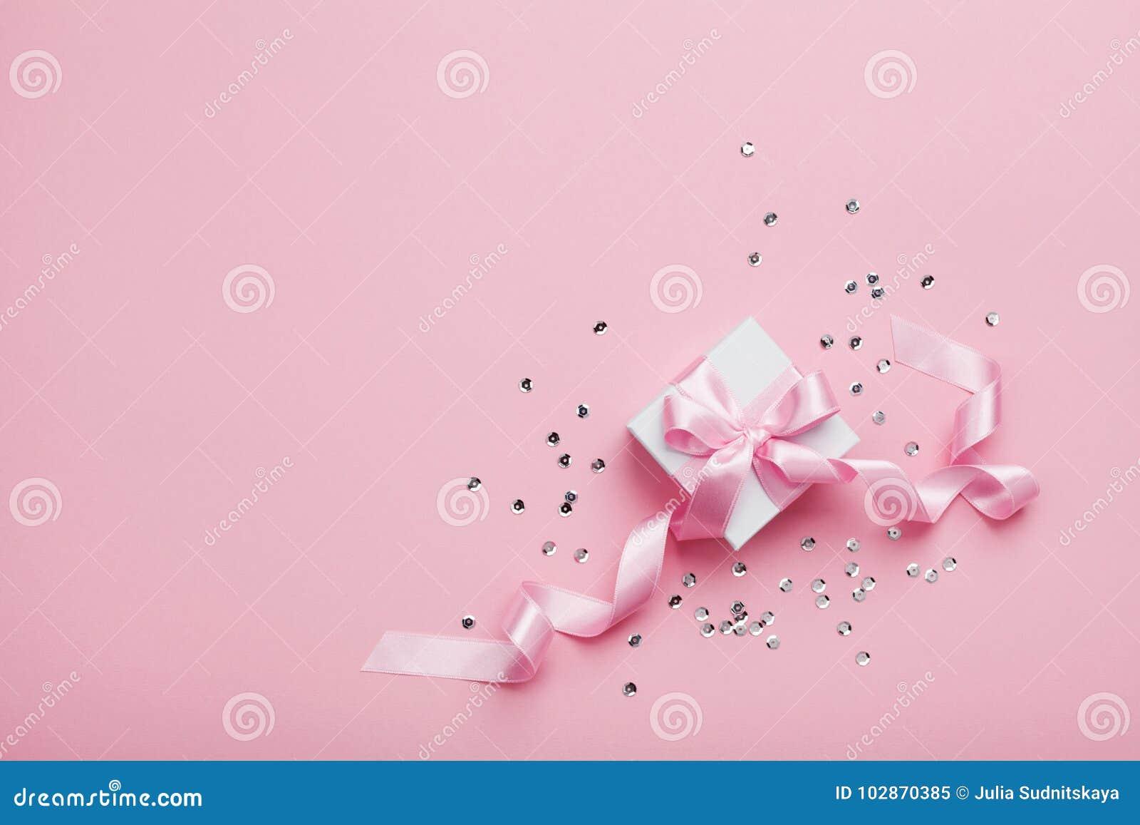 Regalo o actuales caja y lentejuelas en la opinión de sobremesa rosada Endecha plana Concepto del cumpleaños, de la boda o de la
