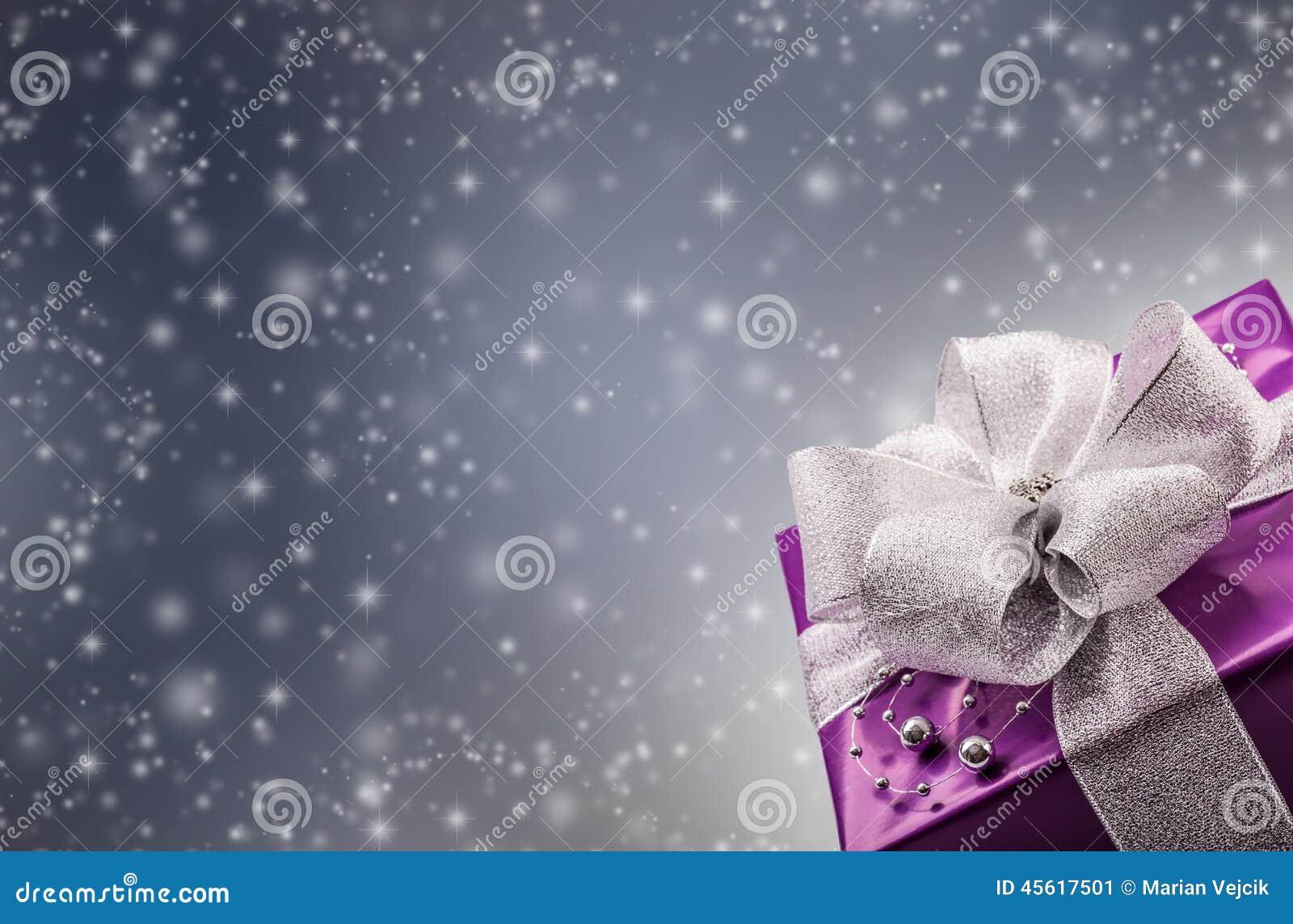 Regalo púrpura de la Navidad o de la tarjeta del día de San Valentín con el fondo de plata del gris del extracto de la cinta