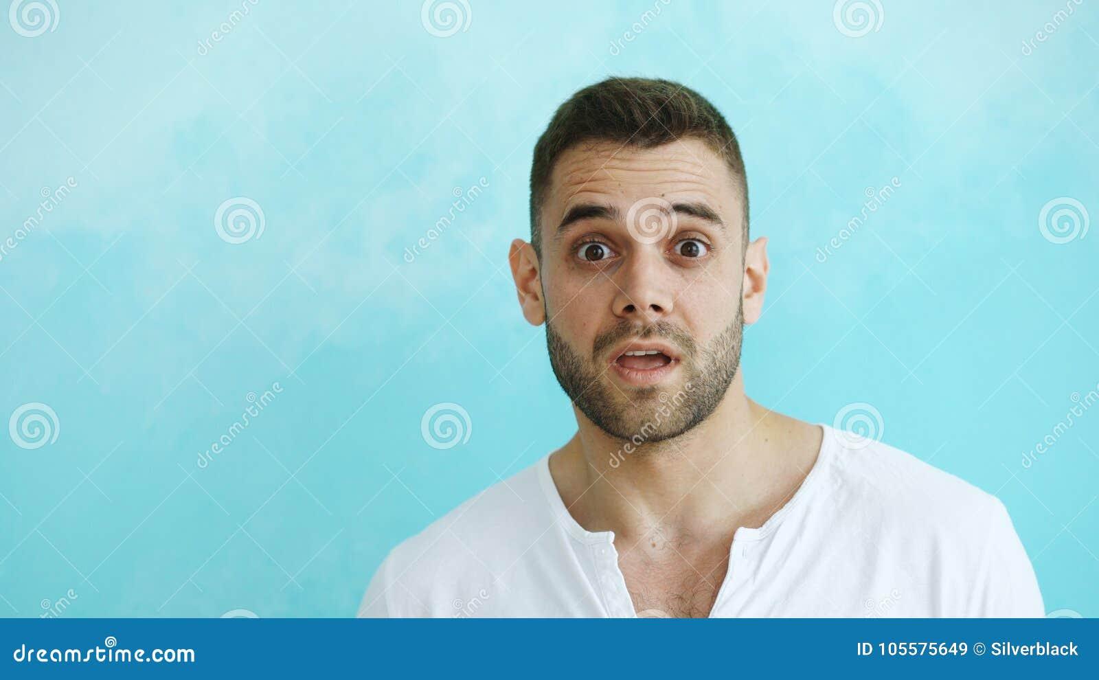 Regard étonnant et se demandant de portrait de jeune homme activement dans l appareil-photo sur le fond bleu