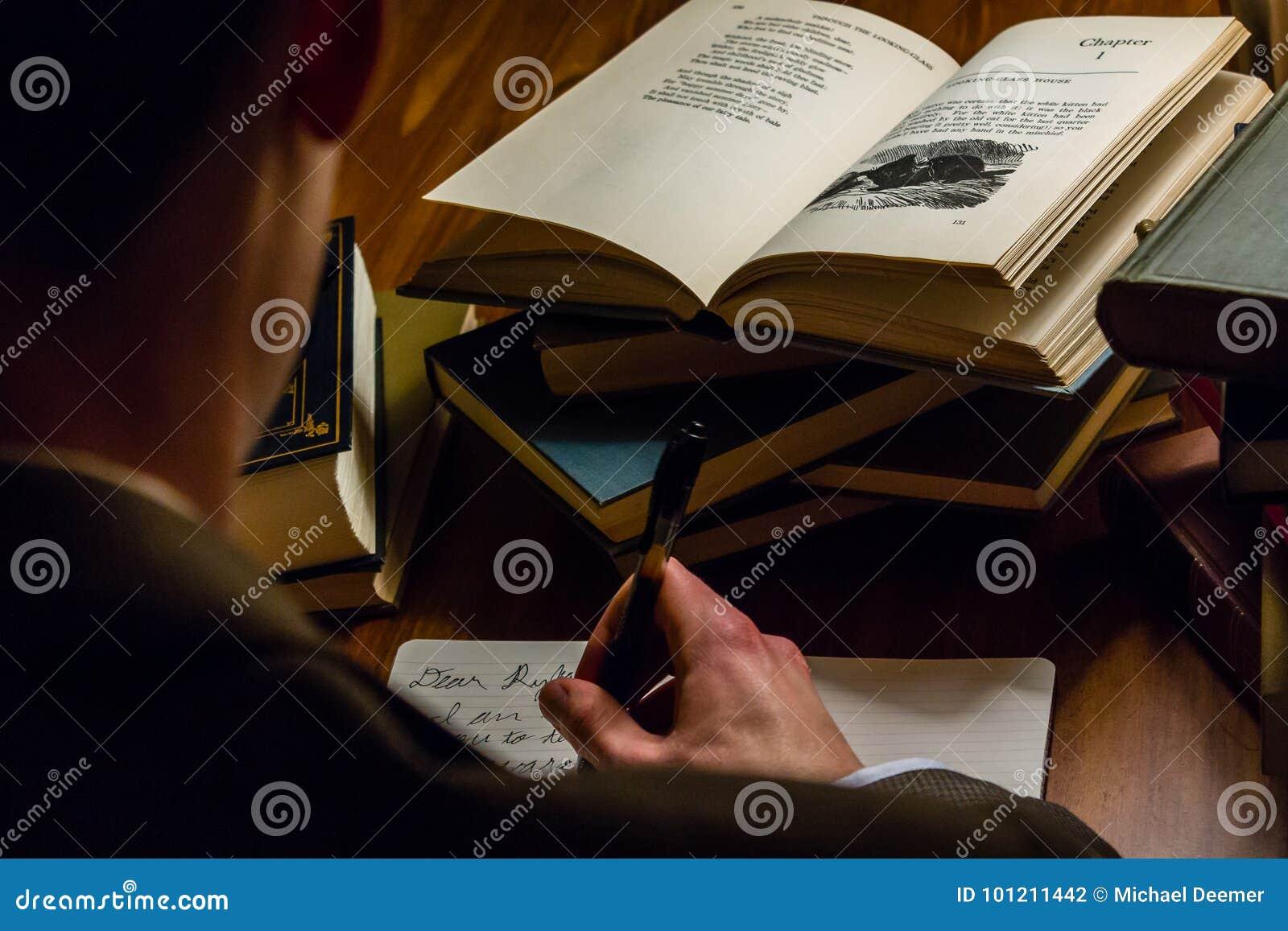 Regard au-dessus de l épaule d un homme écrivant une lettre tout en lisant les ouvrages littéraires