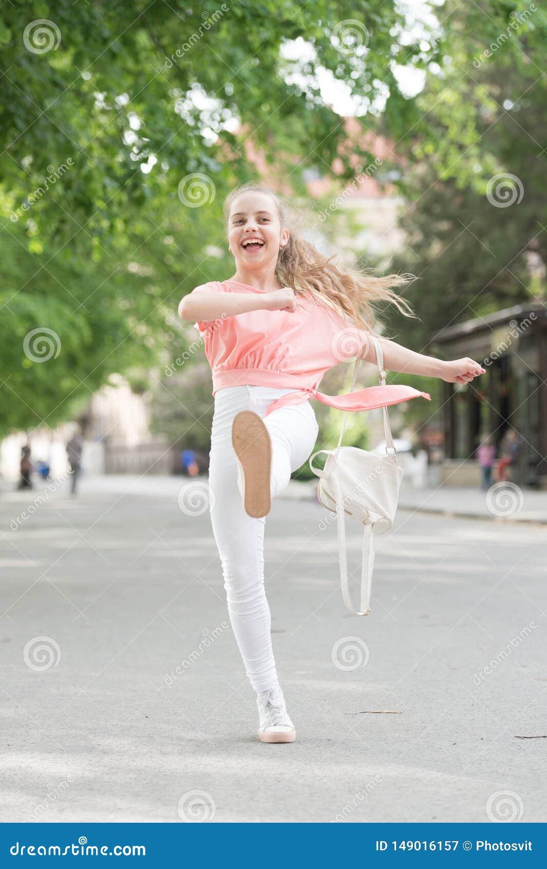 Regard occasionnel Petite fille heureuse marchant le long de la rue dans des v?tements occasionnels et confortables Peu enfant mi