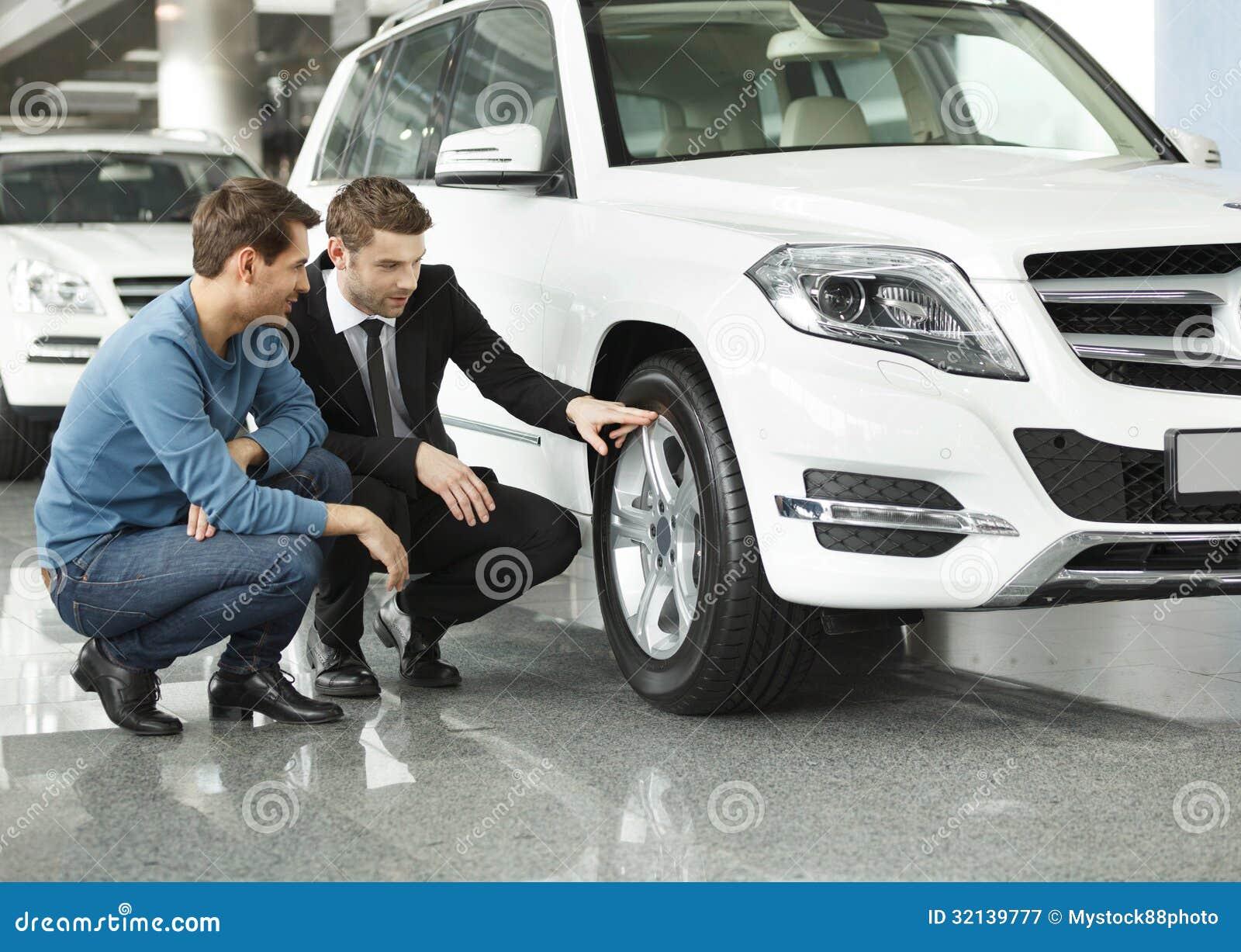 regardez ces pneus jeune vendeur de voiture montrant les avantages o image stock image du. Black Bedroom Furniture Sets. Home Design Ideas
