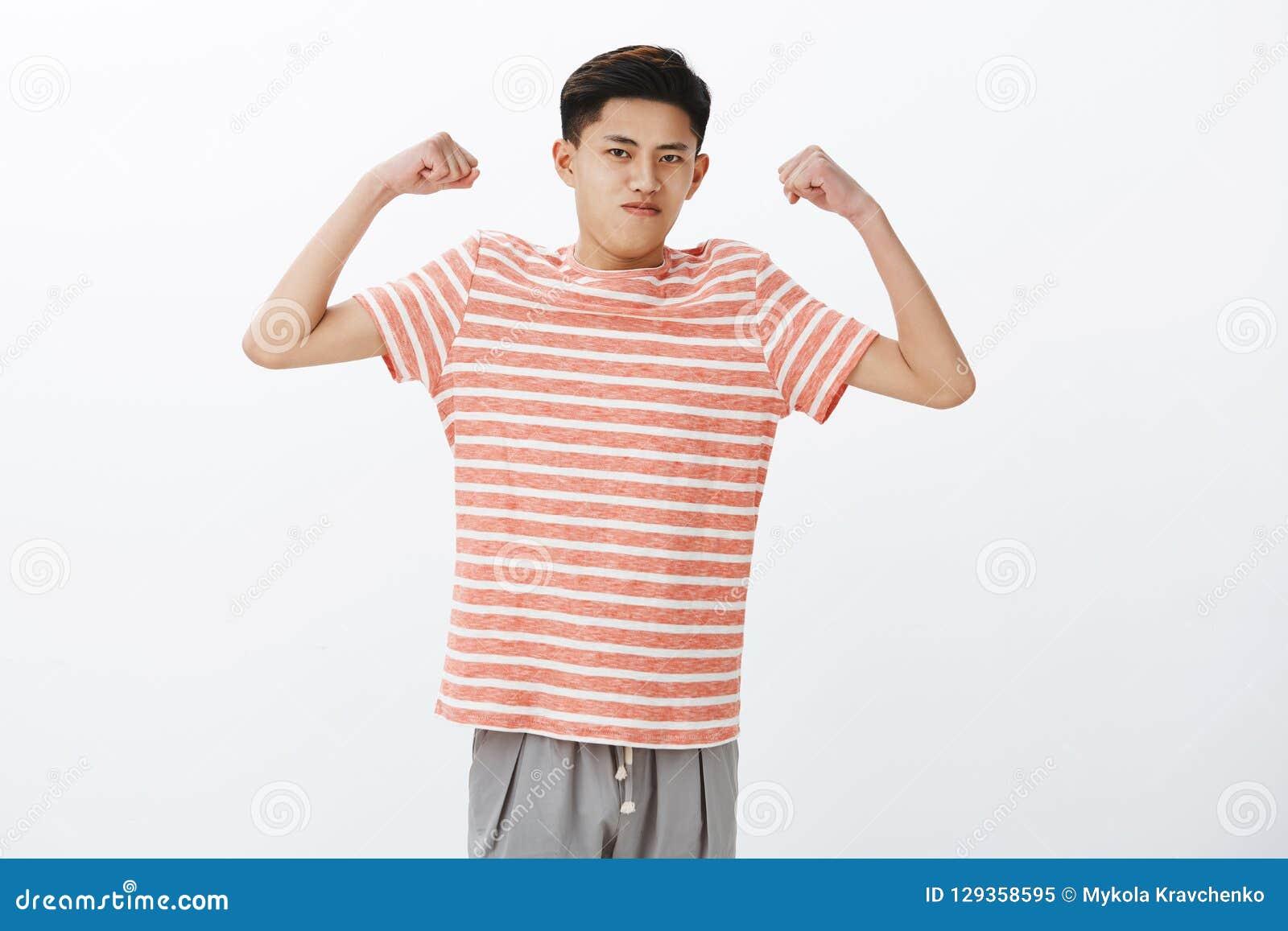 Regardez comme j intense suis Portrait du jeune type asiatique mince drôle assuré soulevant des mains pour montrer le biceps ou l