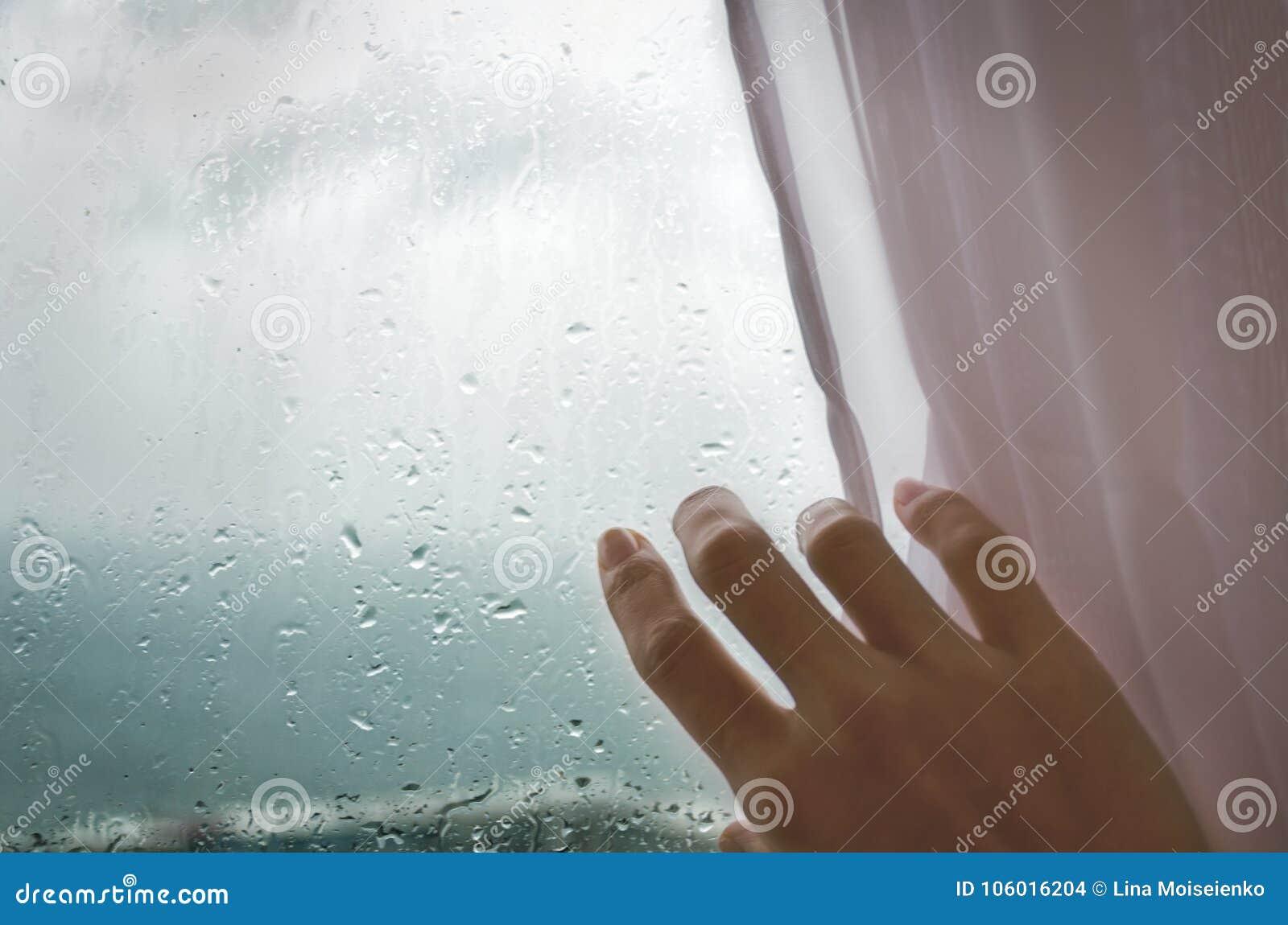 Regenachtig weer - een vrouwen` s hand trekt blinden van het regenachtige venster