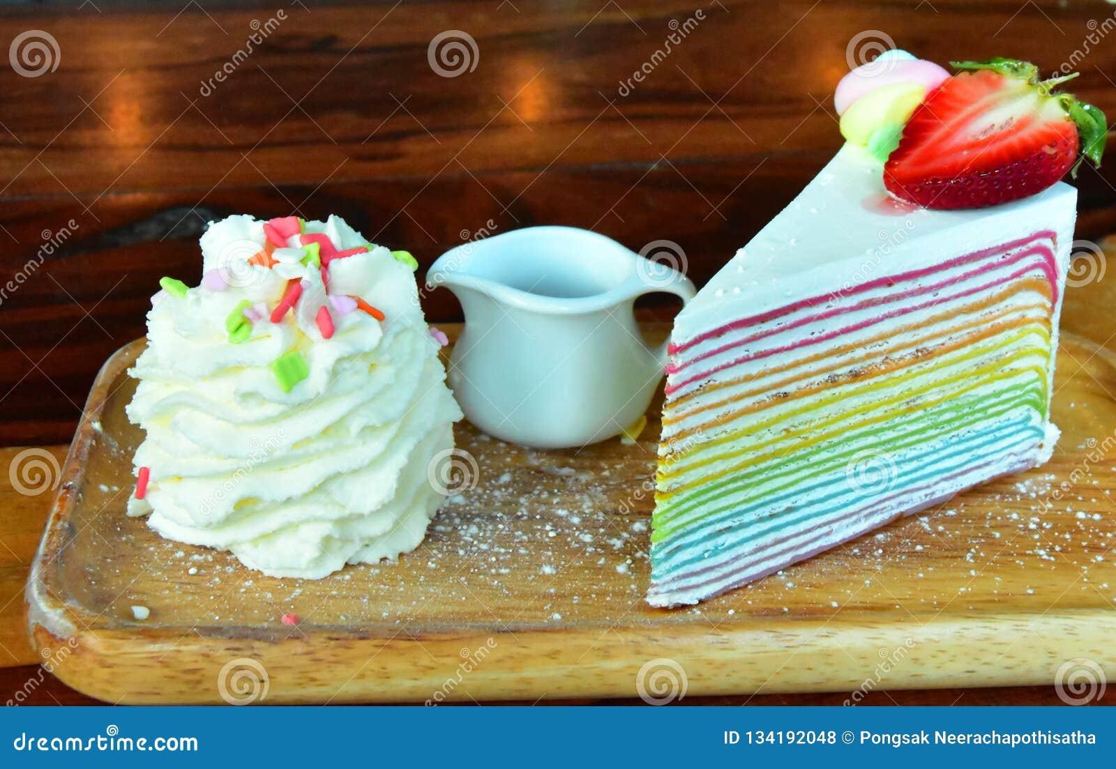 Regenbogen-Erdbeerkrepp Kuchen auf dem Tisch