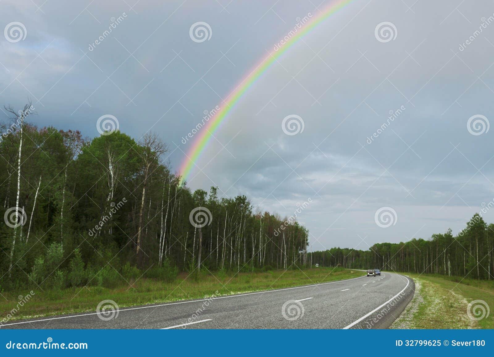 Regenboog na regen over weg