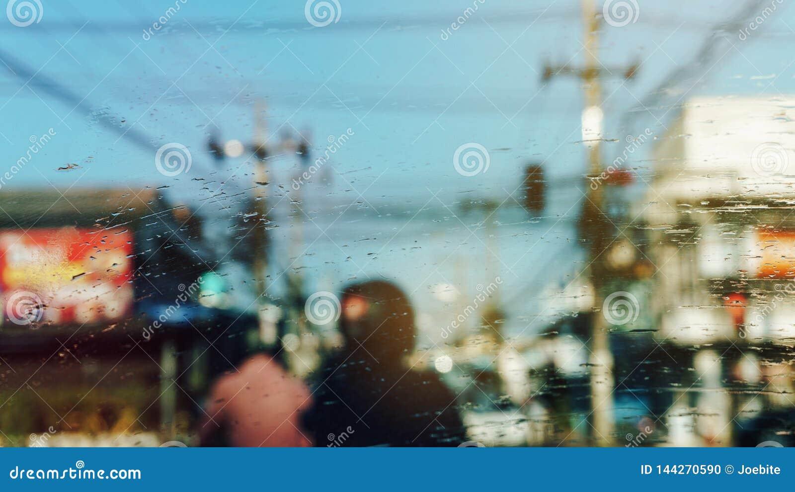 Regendruppeltjes op autowindscherm, in een vaag geblokkeerd verkeer abstracte achtergrond Vuile ruitewisserbladen Slecht weer