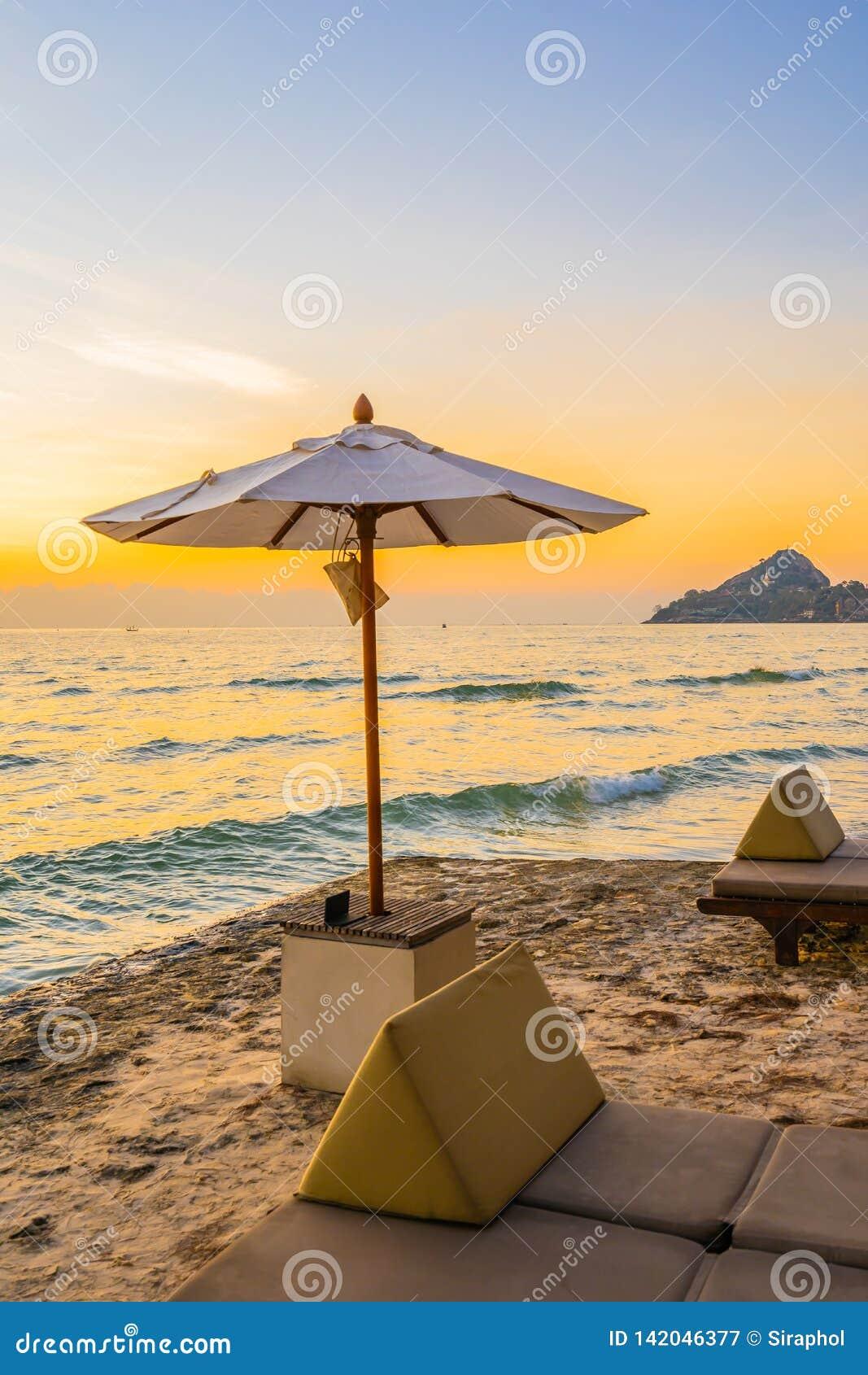 Regenschirm und Stuhl mit Kissen um schöne Landschaft des Strandes und des Meeres