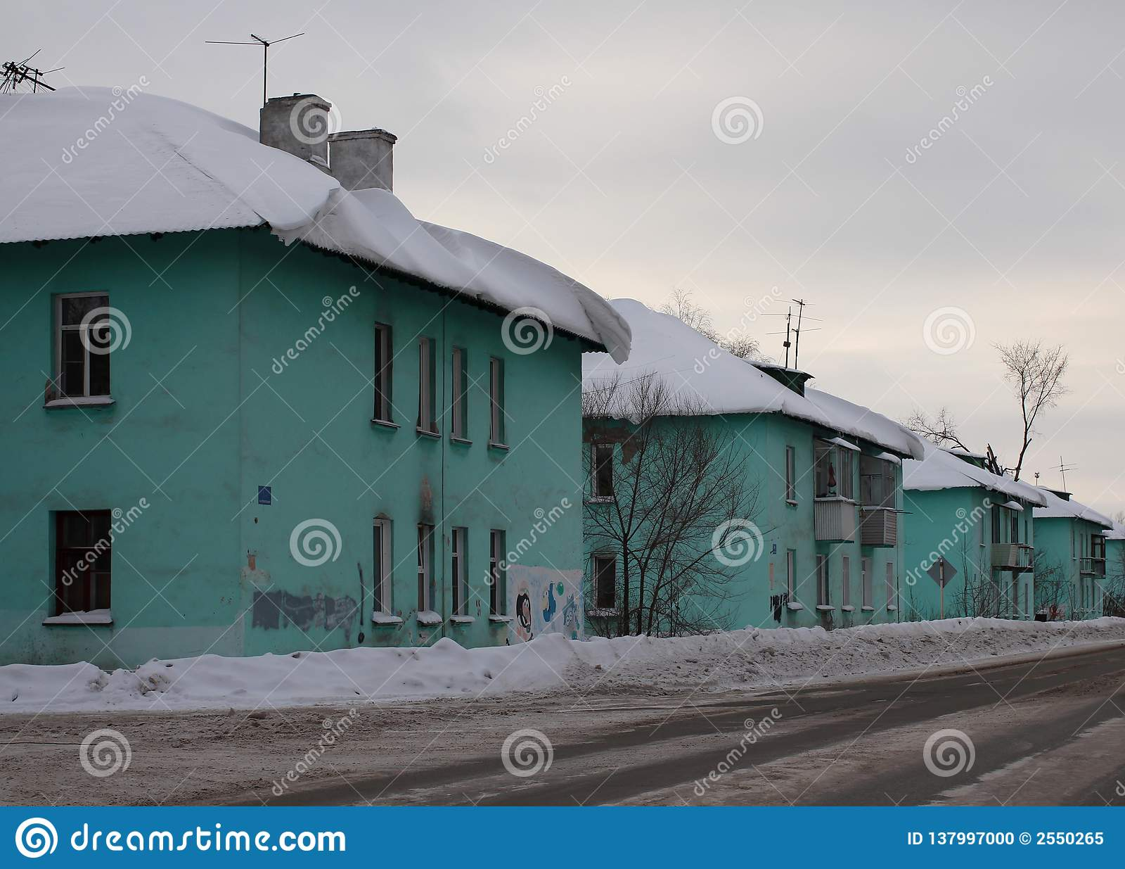 Región urbana de las pequeñas casas idénticas viejas la ciudad de Ob a lo largo de la calle un día de invierno gris, cubierto