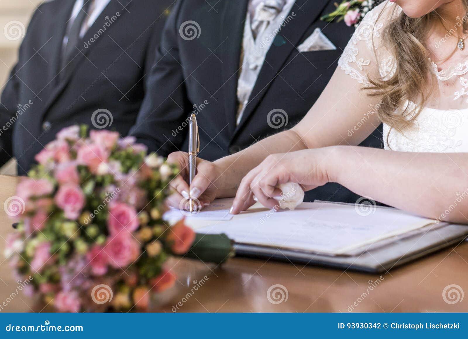 Registro de firma de la novia de la boda, pluma de tenencia y pares elegantes de la boda del documento oficial