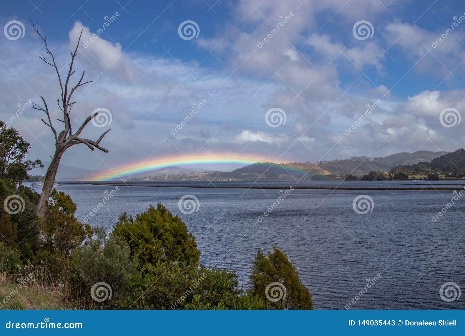 Regnbåge över land på kängurufjärden, Tasmanien