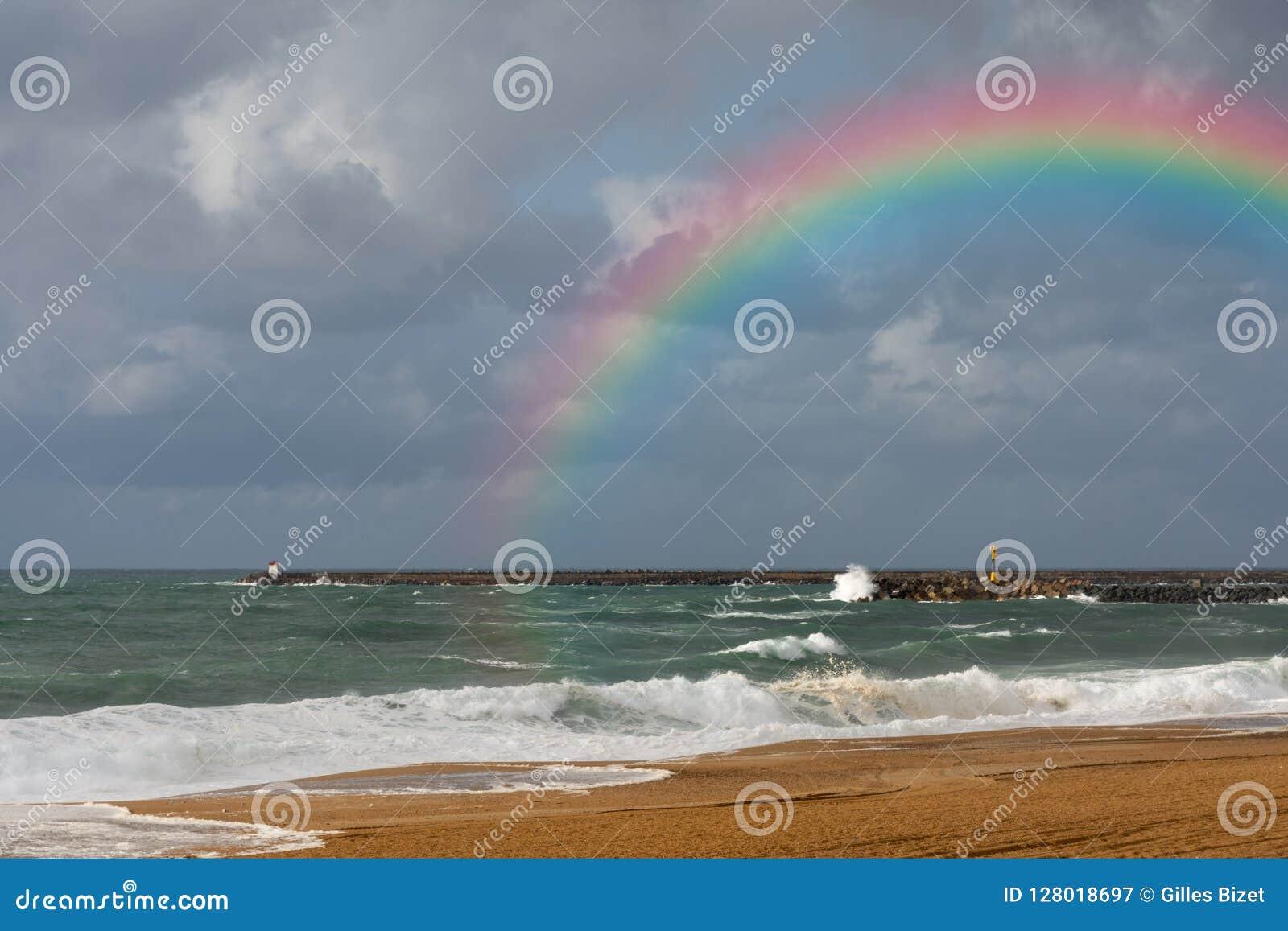 Regnbåge på stranden av Anglet efter stormen
