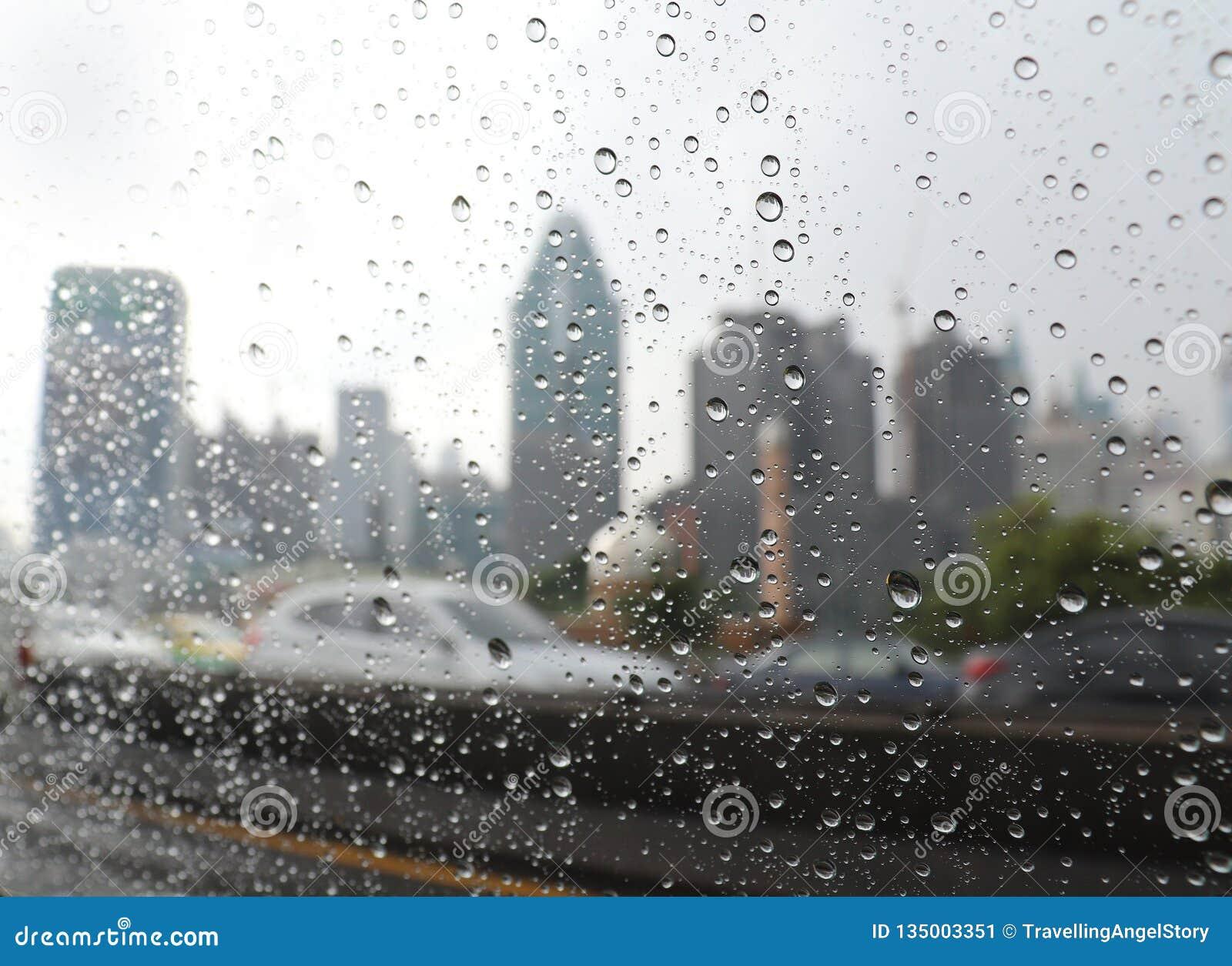 Regndroppar i bilfönstret på den Bangkok huvudvägen
