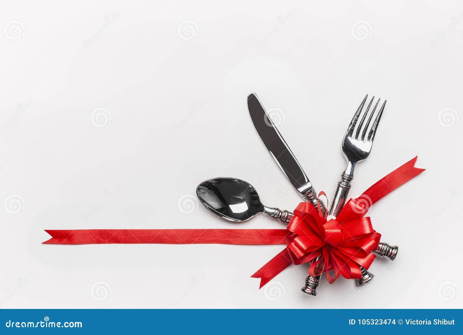 Regolazione di posto festiva della tavola con la coltelleria e l arco rosso e nastro su fondo bianco, insegna Disposizione per la