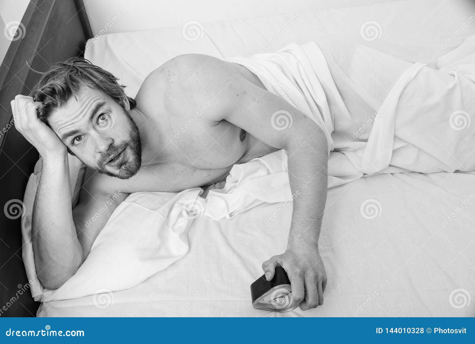 Regulate your bodys clock. Sleep regime habit. Man unshaven lay bed hold alarm clock. Man unshaven bearded wakeful face