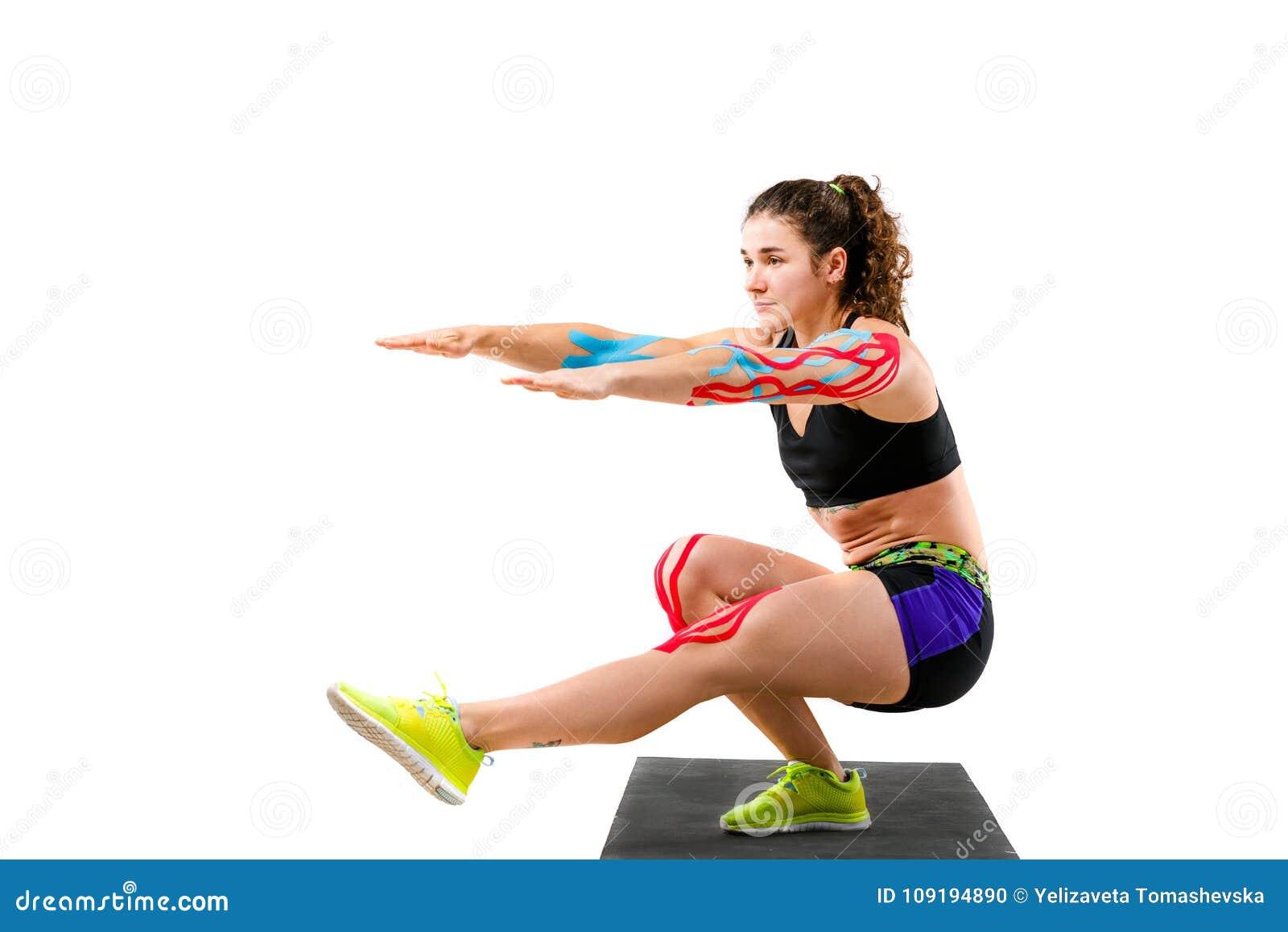 Rehabilitación de la cinta de la kinesiología del tema de atletas Muchacha hermosa con el botín hermoso que hace la manta del onb