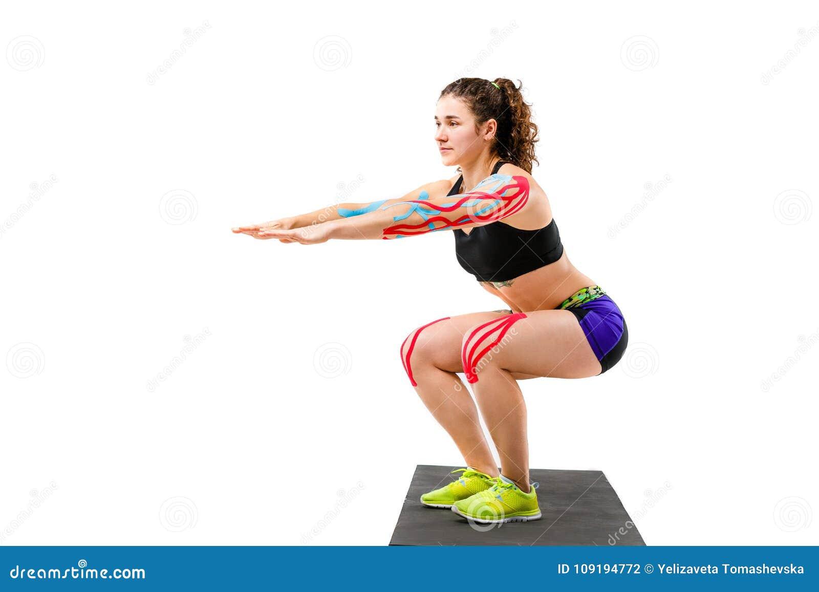 Rehabilitering för temakinesiologyband och hälsa av idrottsman nen Härlig flicka som gör en satt övning på en svart filt på en vi