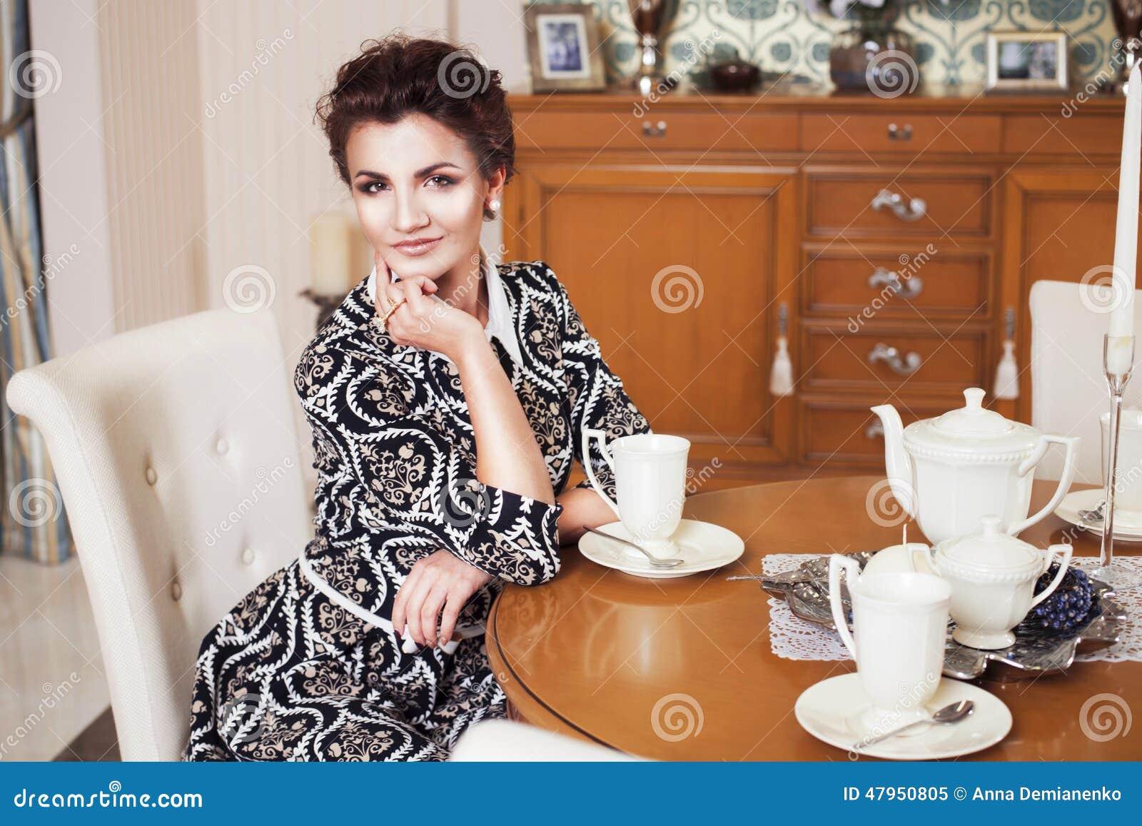 Reiche freche Frau des schönen Brunette im eleganten Kleid, das auf einem Stuhl in einem Raum mit klassischem trinkendem Innenwei