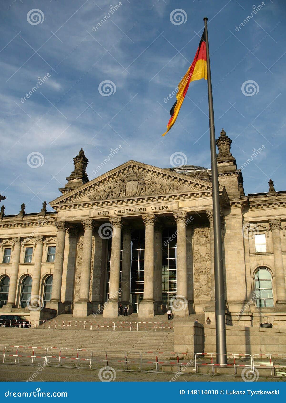 Reichstag-Gebäude in Berlin, in Deutschland und in der deutschen Flagge in der Front