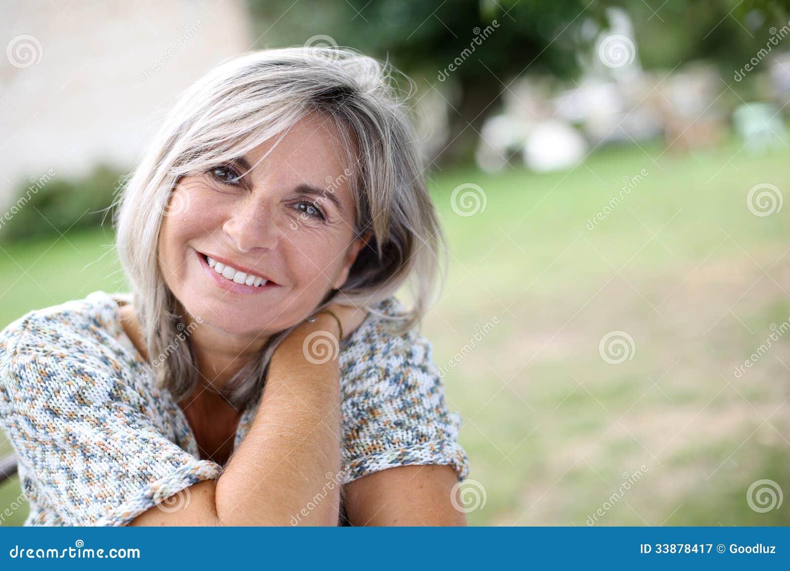 Reife Frau Mit Einem Ruhigen Blick, Der Im Garten Sitzt