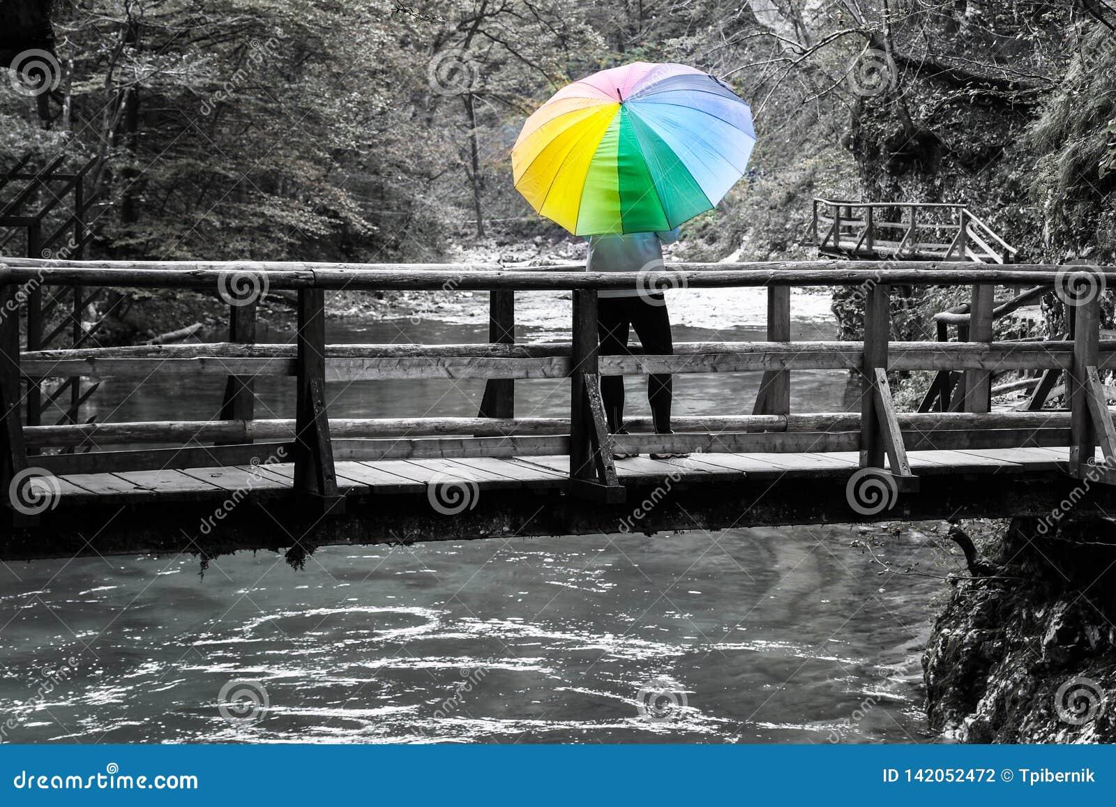 Reife Frauenstellung auf einer Holzbrücke über Fluss mit buntem Regenschirm an einem sonnigen Herbsttag
