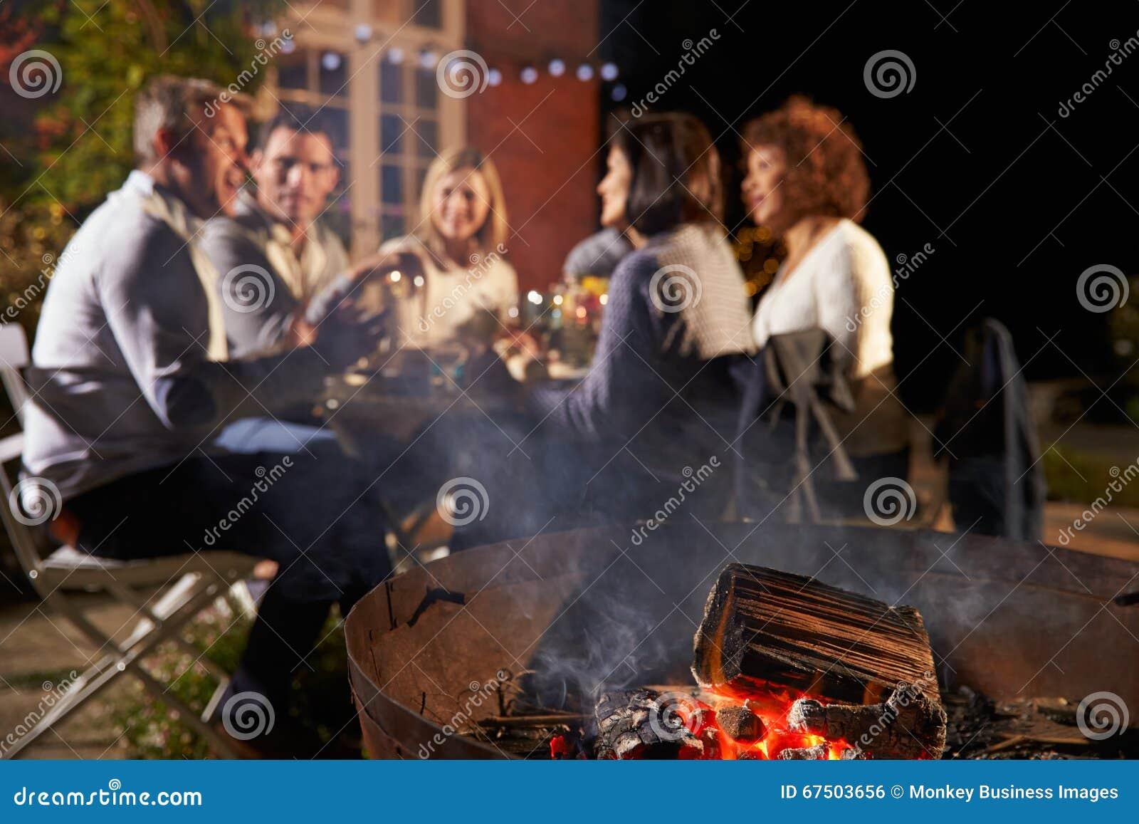 Reife Freunde, die Abendessen im Freien um Firepit genießen
