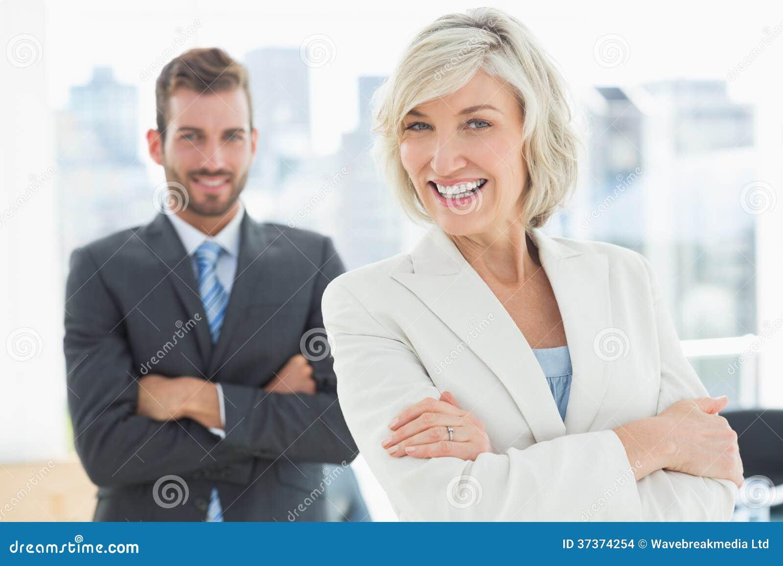 Reife Geschäftsfrau und junger Mann mit den Armen gekreuzt
