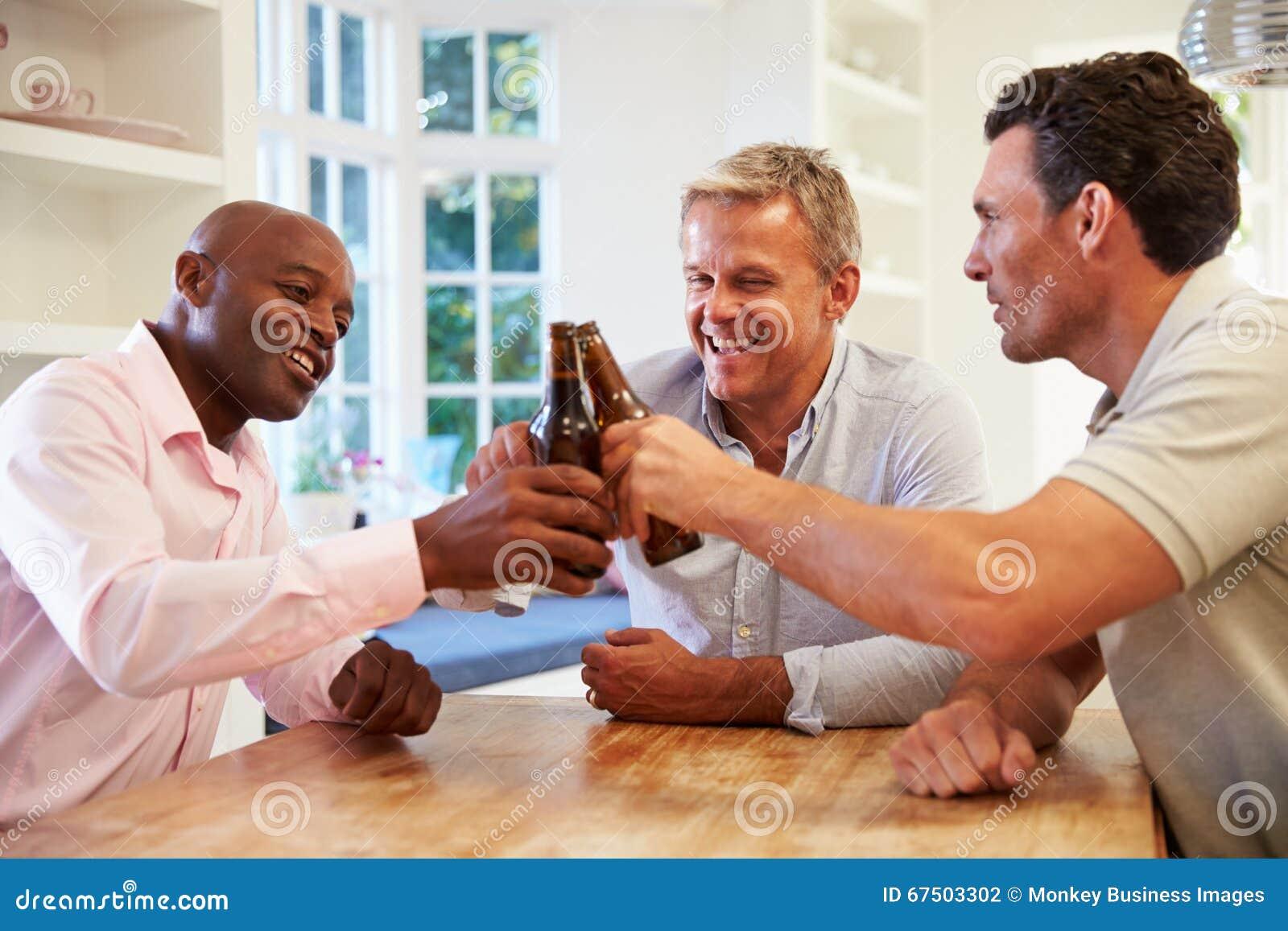 Reife männliche Freunde Sit At Table Drinking Beer und Unterhaltung