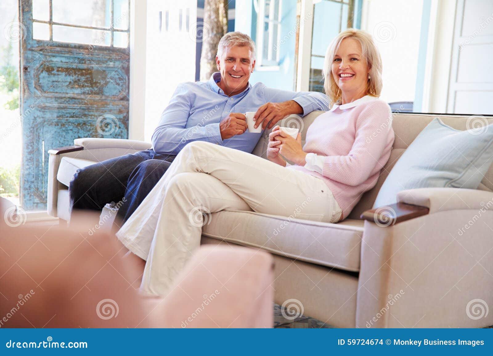 Reife Paare zu Hause, die im Aufenthaltsraum mit heißem Getränk sich entspannen