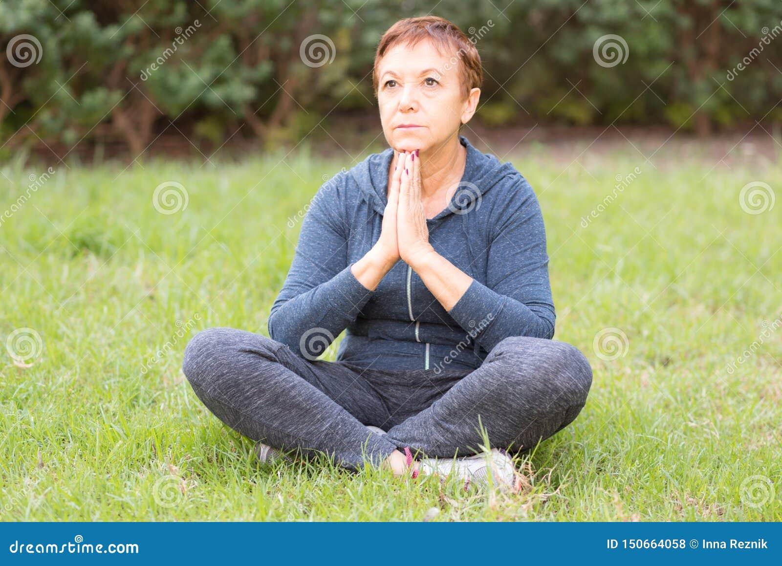 Reife schöne aktive glückliche Frau morgens im Park, entspannen sich nach Sportübungen Mittlere Dame in der Yogahaltung