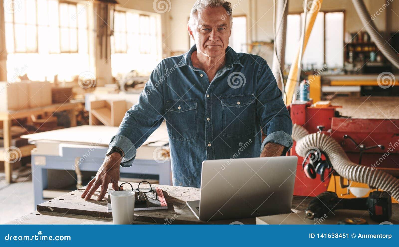 Reifer männlicher Tischler in seiner Werkstatt