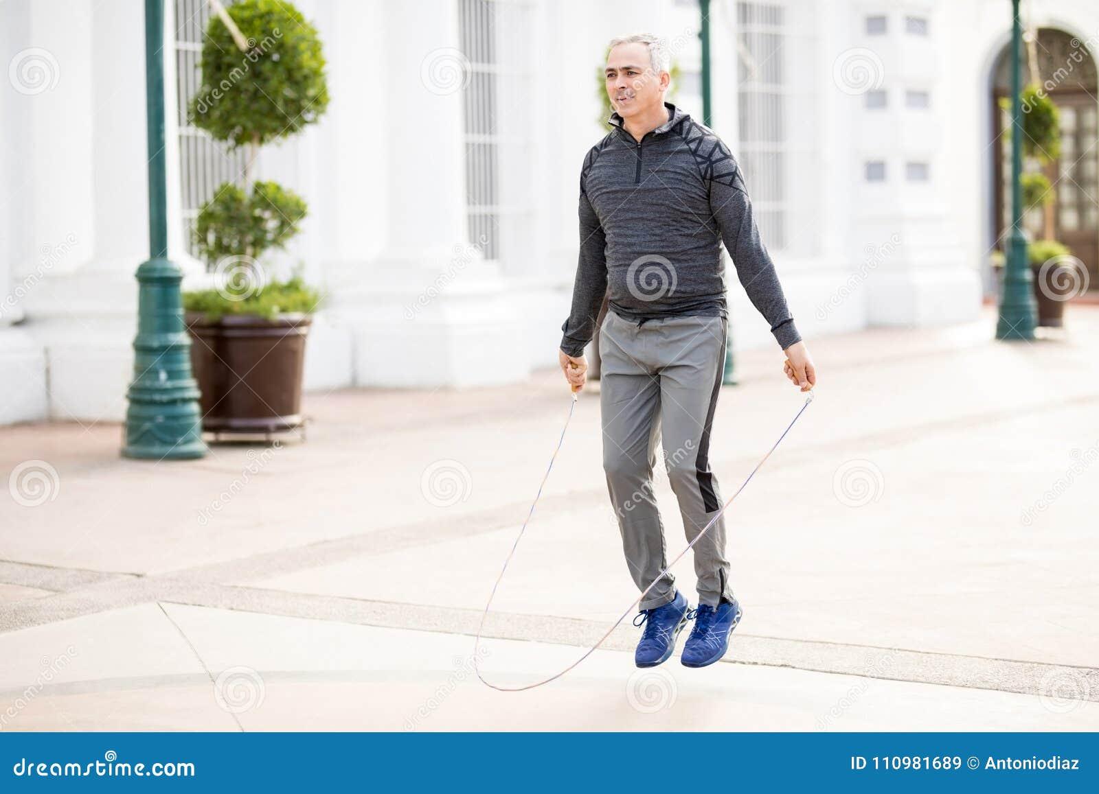 Reifer Mann, der ein Seil springt und draußen trainiert