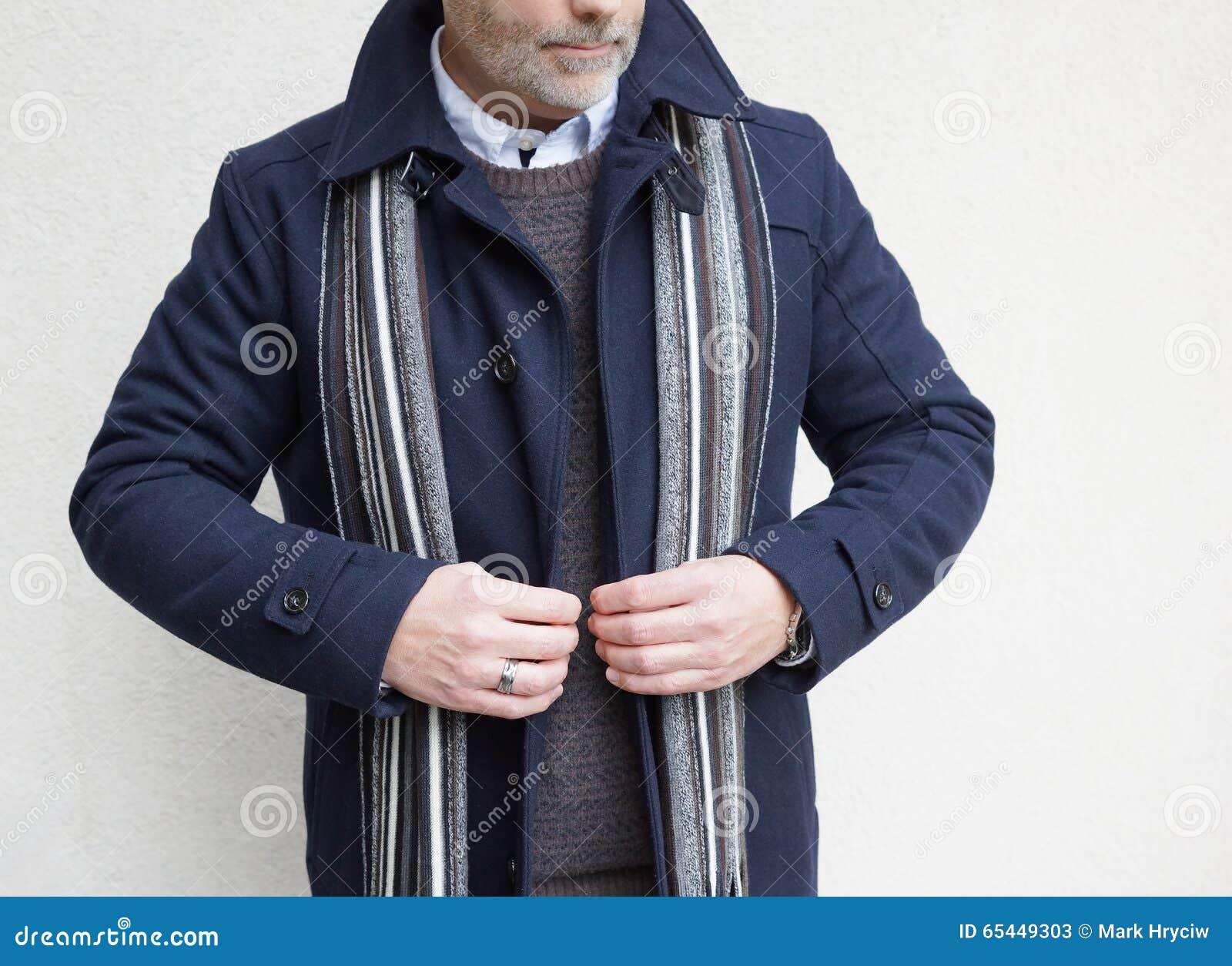 Reifer Mann, der seine Jacke steht und knöpft